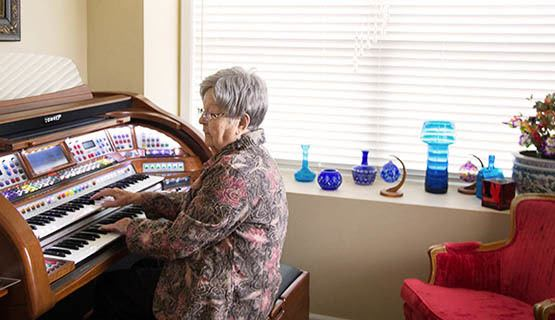 A resident playing a piano at The Heritage at Fountain Point in Norfolk, Nebraska