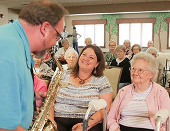 A guest playing the saxophone for residents at The Heritage at Fountain Point in Norfolk, Nebraska