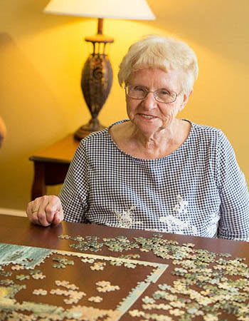 A happy resident with a puzzle at The Heritage at Fountain Point in Norfolk, Nebraska