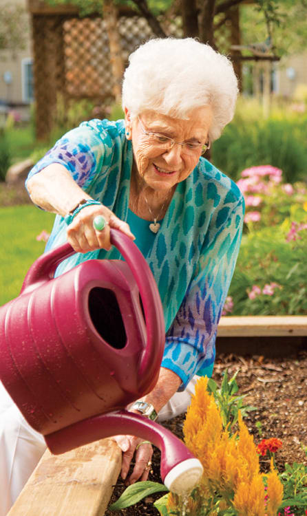 A smiling resident watering a garden at The Heritage at Fountain Point in Norfolk, Nebraska