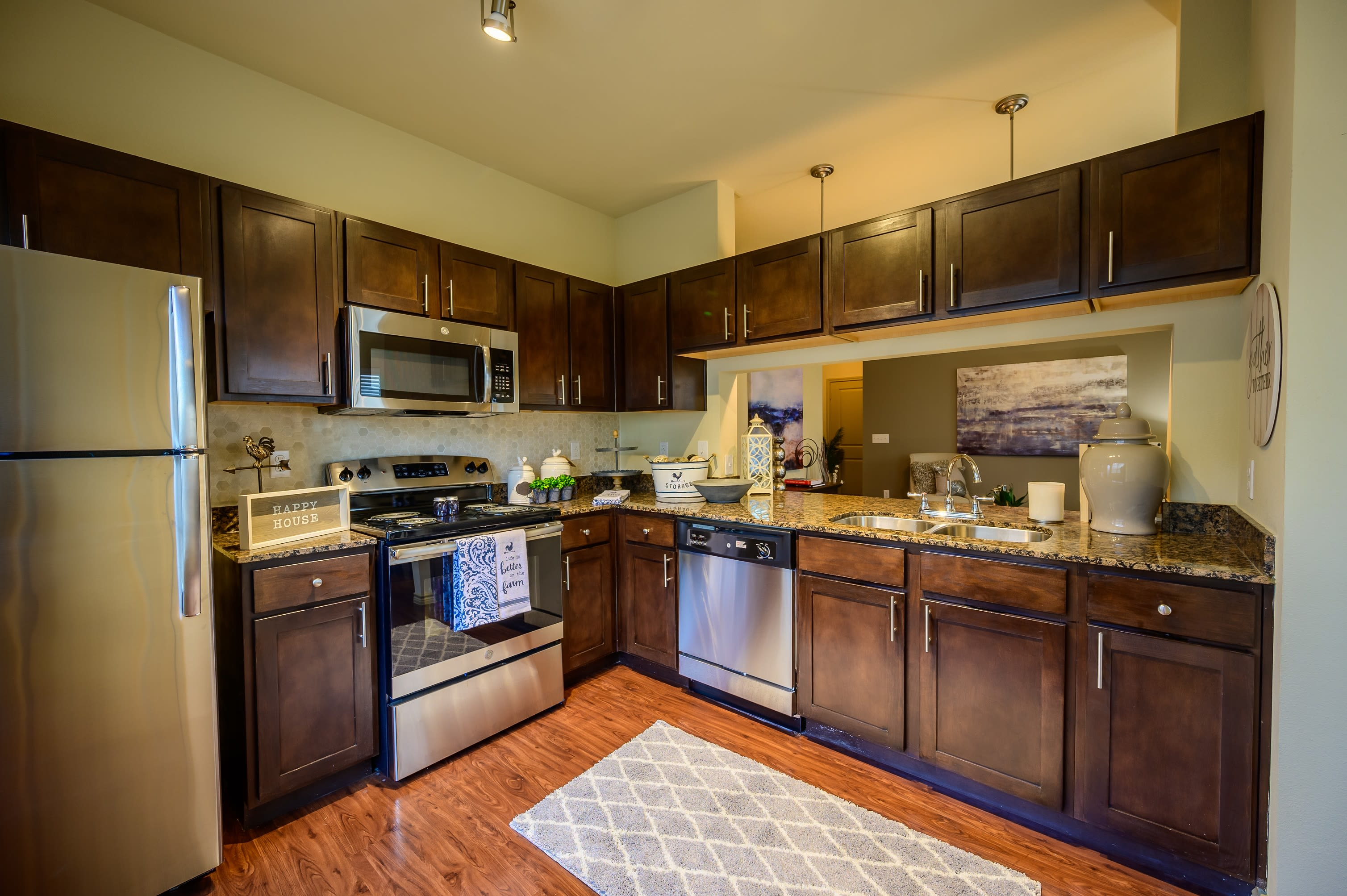 Dark wood cabinetry in model kitchen at Pecan Springs Apartments