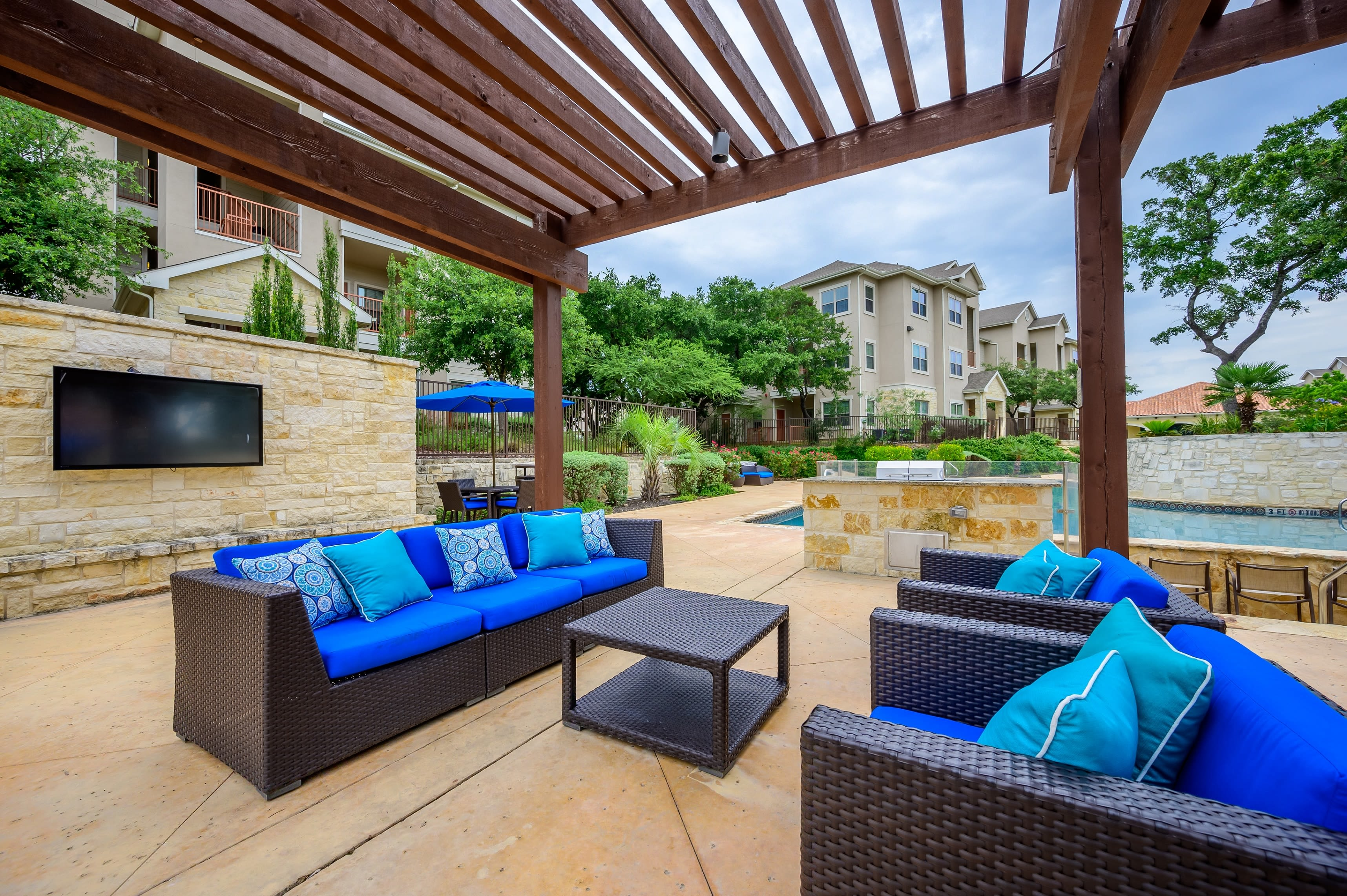 Outdoor seating by pool at Pecan Springs Apartments