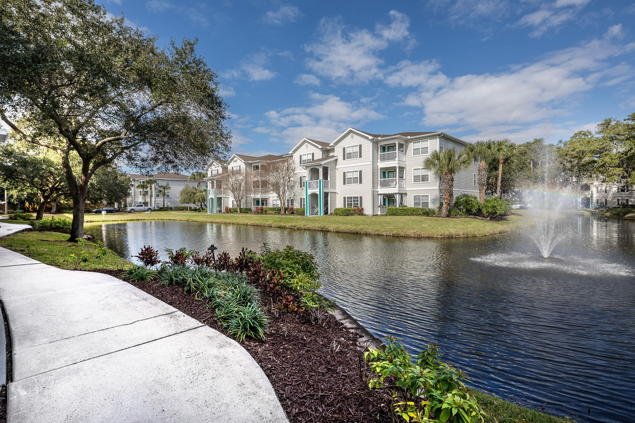 Perimeter sidewalks near large outdoor pond with fountain at Amira at Westly in Tampa, Florida