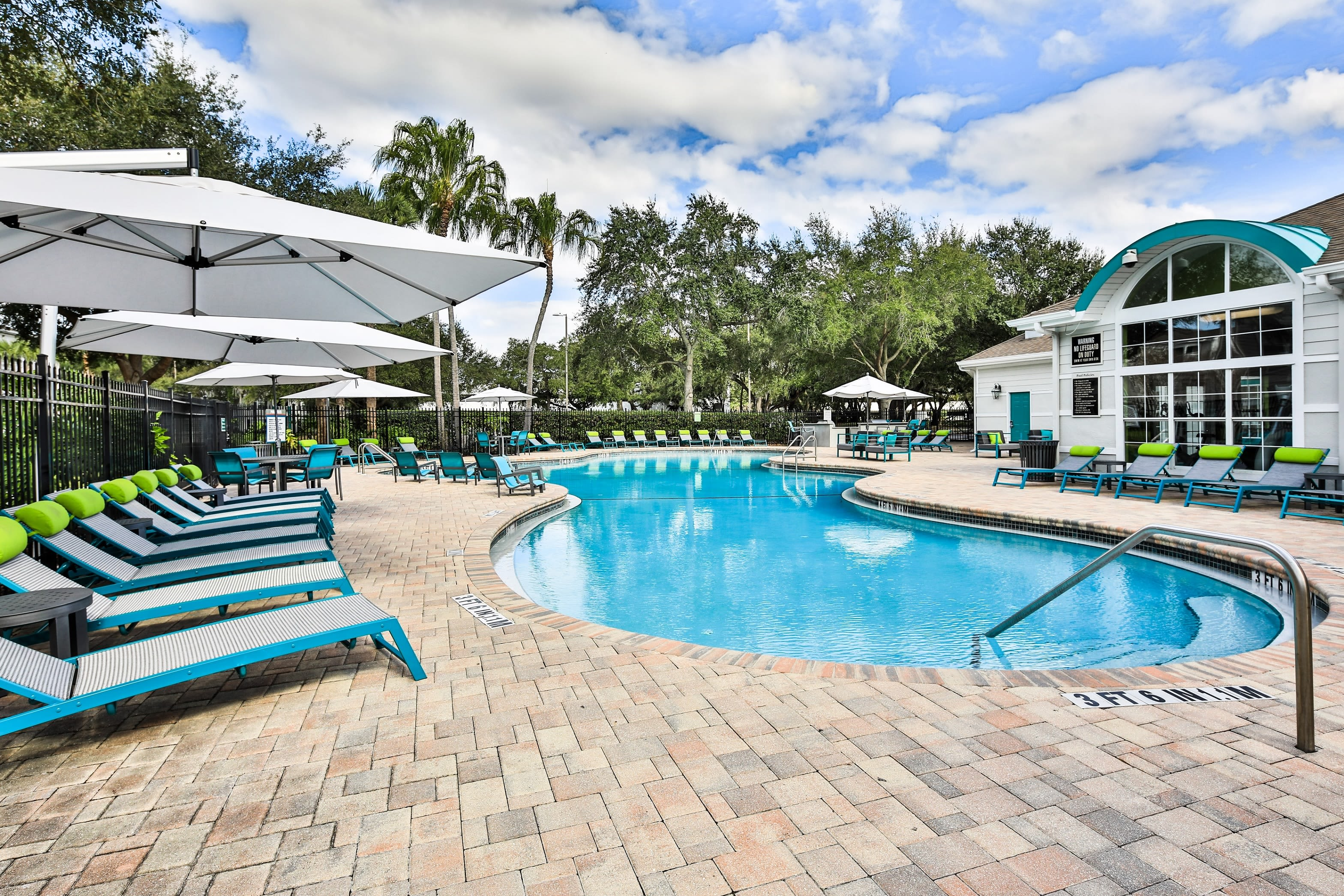 Outdoor pool with lounge chairs and clubhouse at Amira at Westly in Tampa, Florida