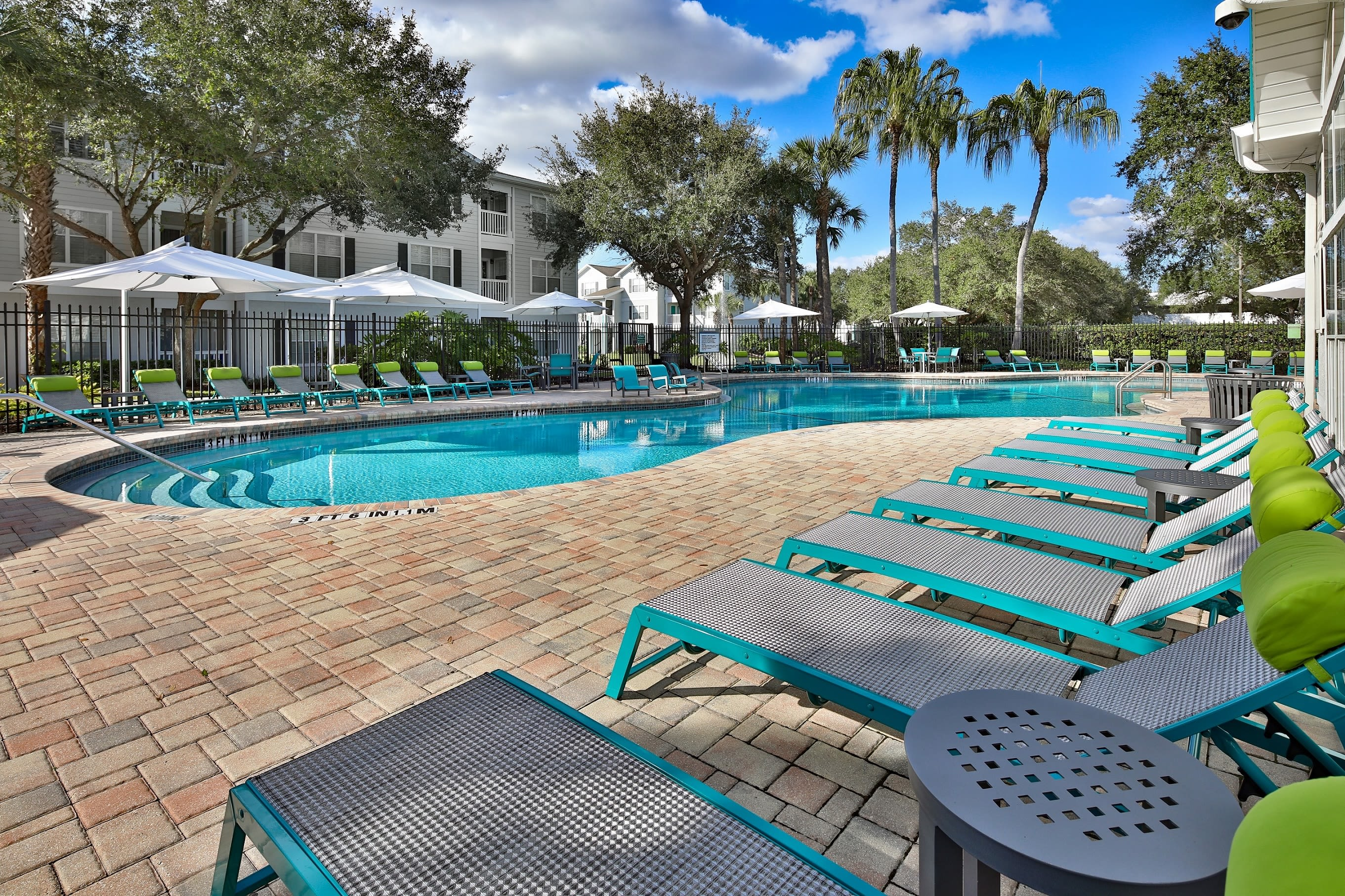 Lounge chairs by outdoor pool at Amira at Westly in Tampa, Florida