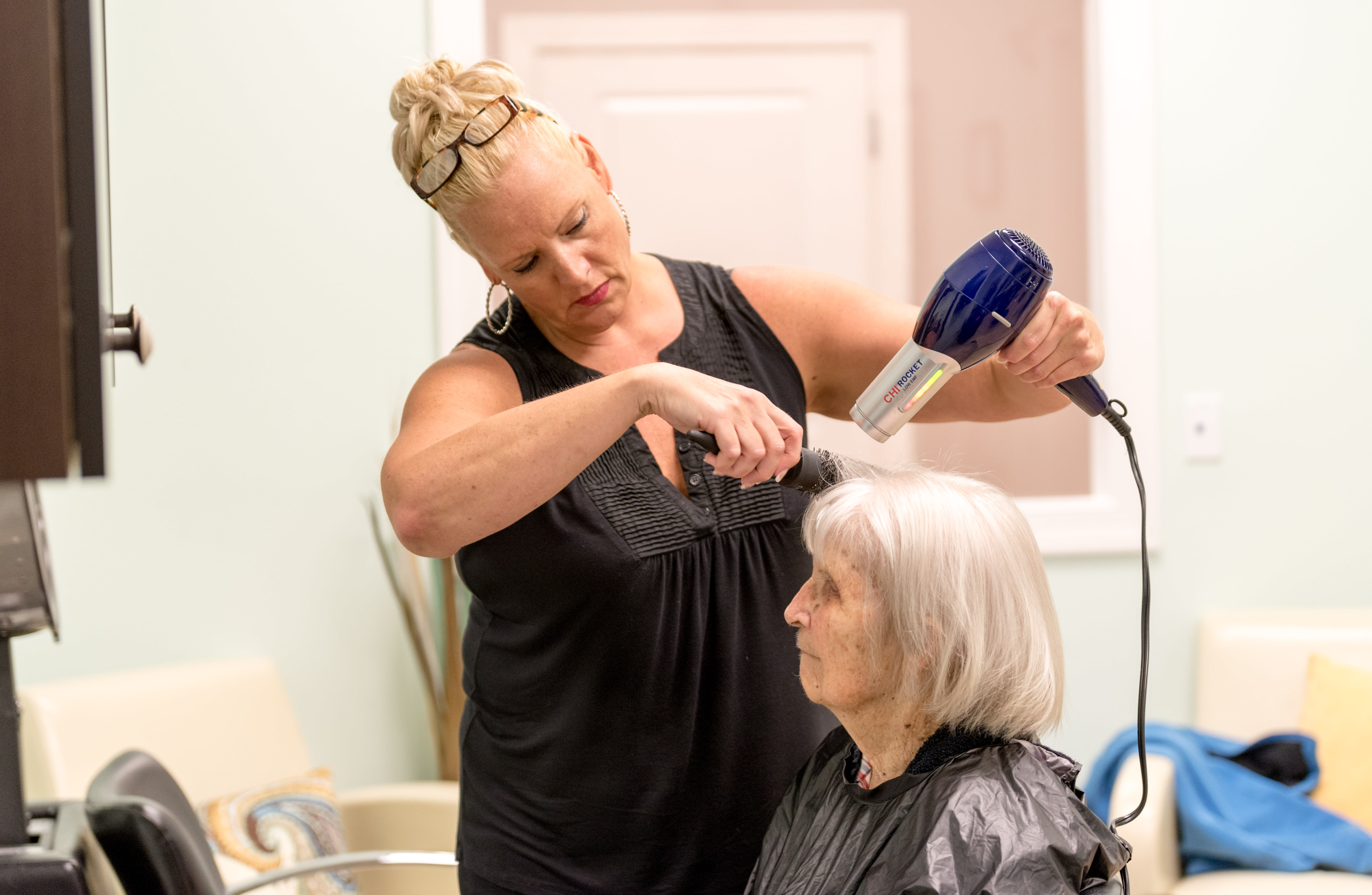 Staff helping resident with hair at Inspired Living at Lakewood Ranch in Bradenton, Florida.
