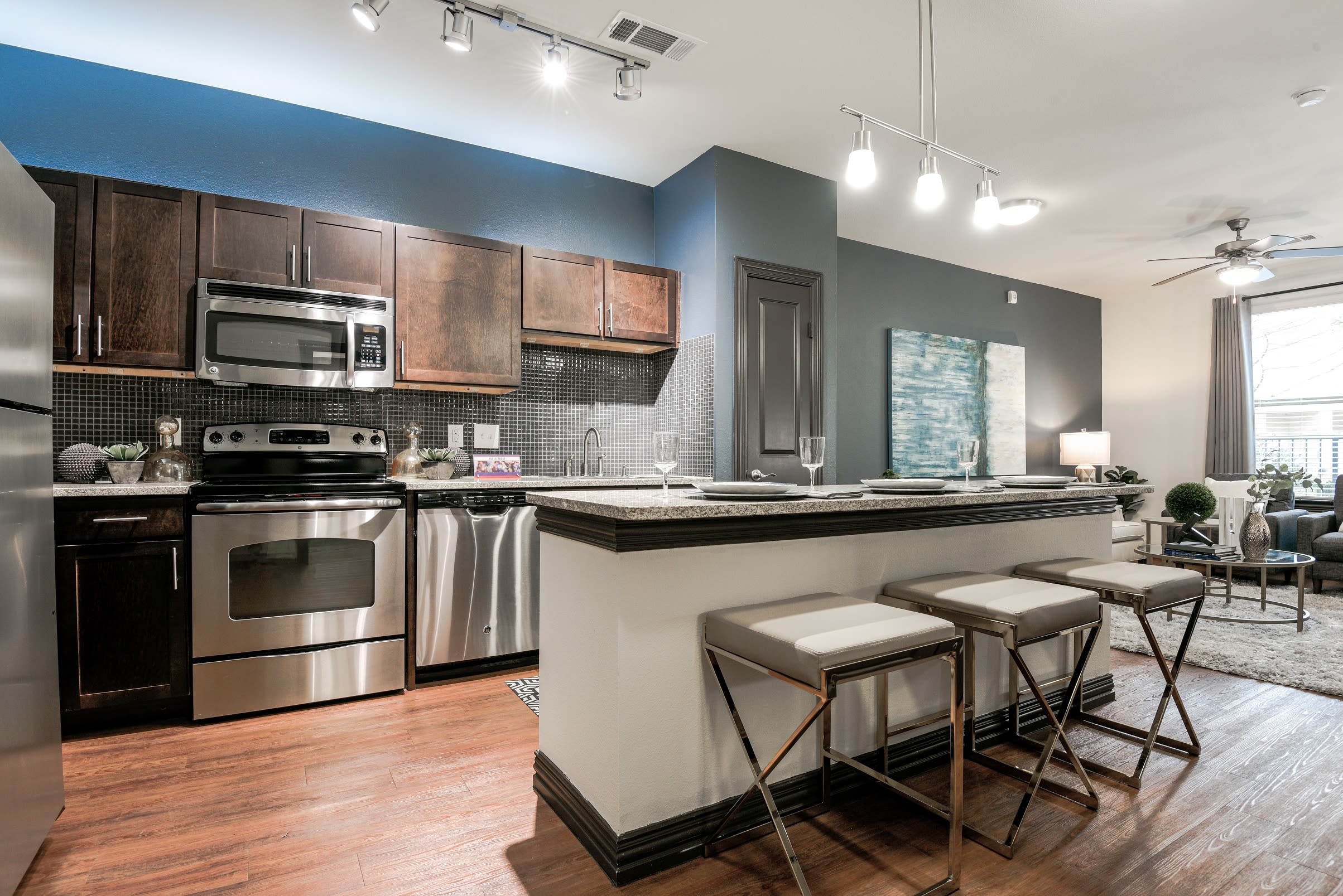 Open-concept floor plan with hardwood floors of model home at The Blvd in Irving, Texas