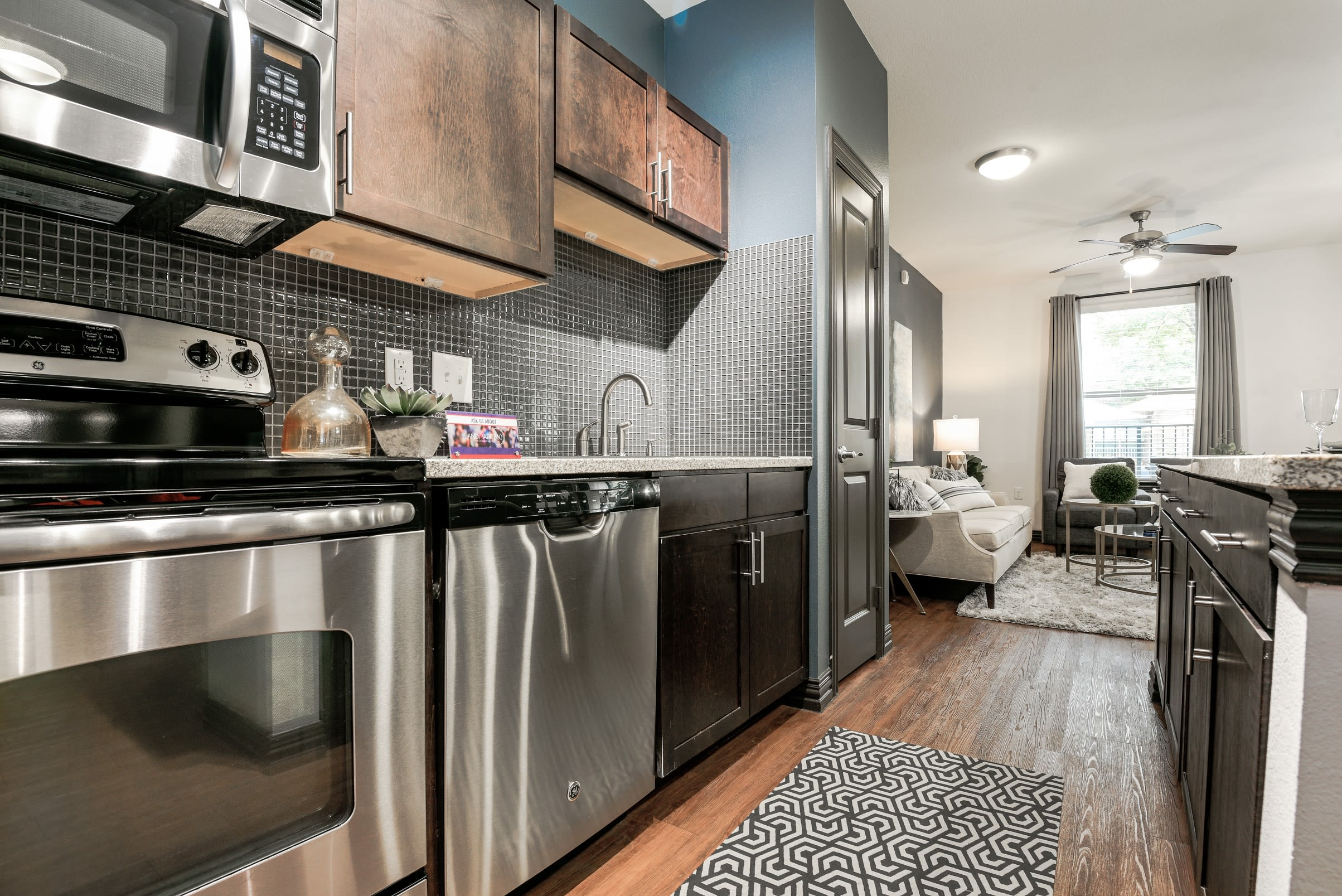 Luxurious kitchen with wood flooring and wood cabinetry at The Blvd in Irving, Texas