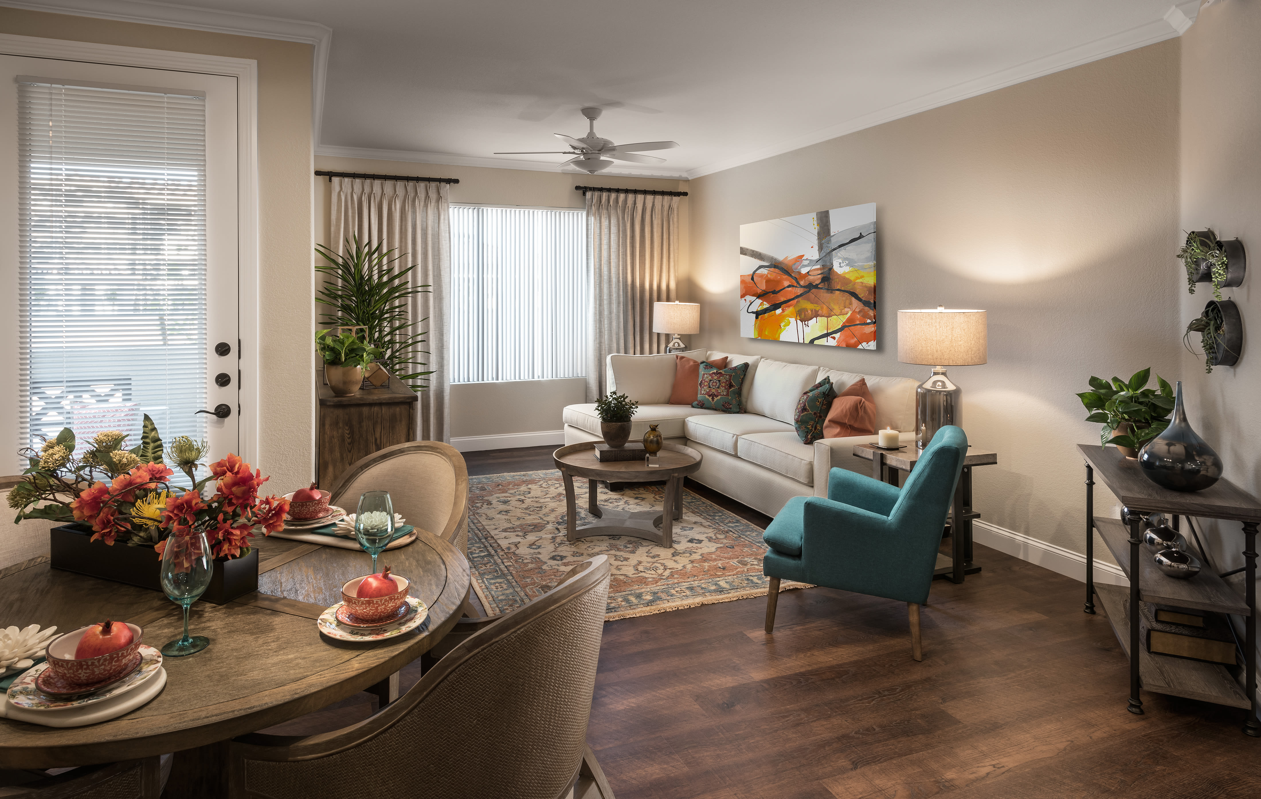 Open-concept layout with hardwood floors and ceiling fan in model home at San Villante in Mesa, Arizona