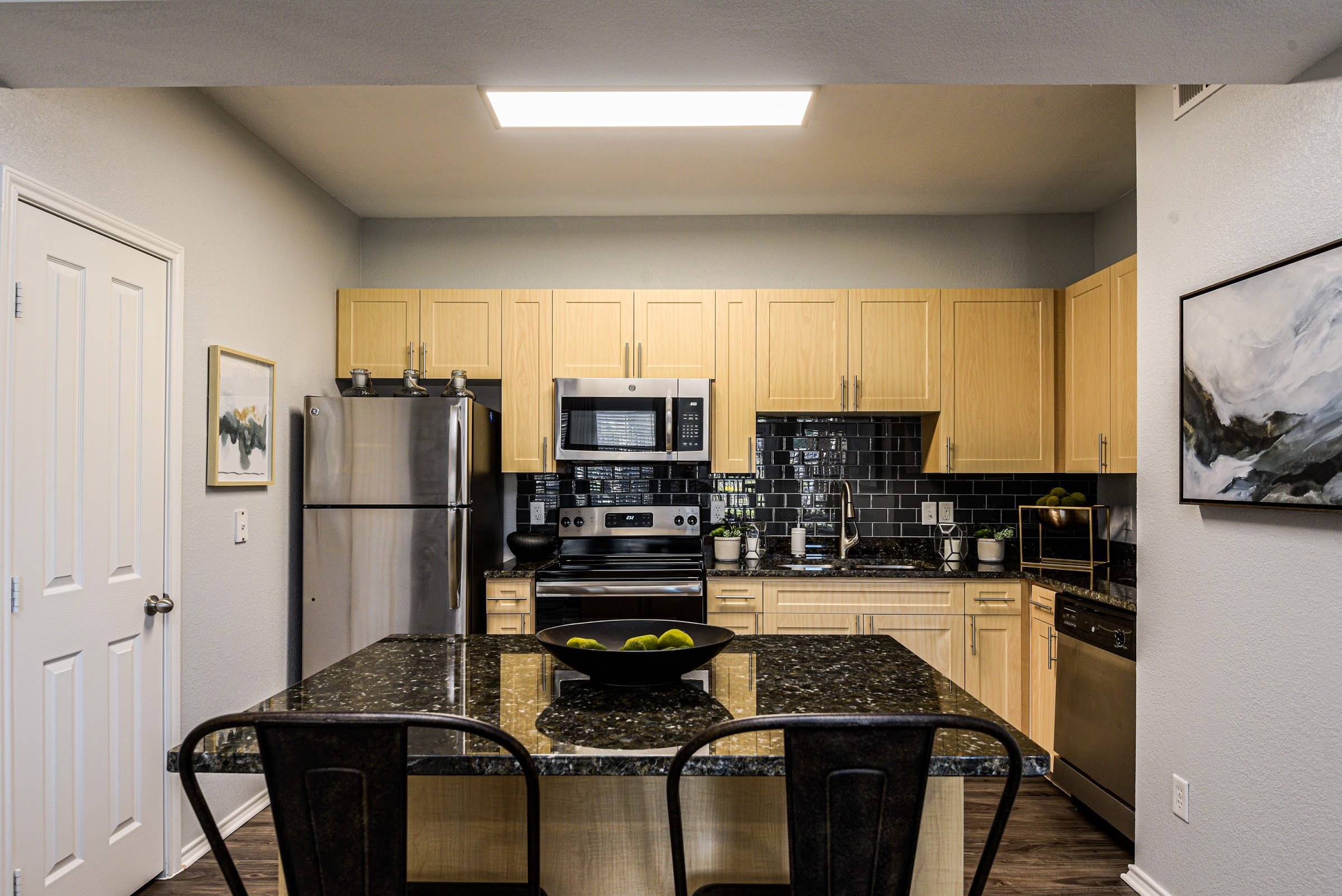 Granite countertop kitchen with island for bar seating at Ranch ThreeOFive in Arlington, Texas