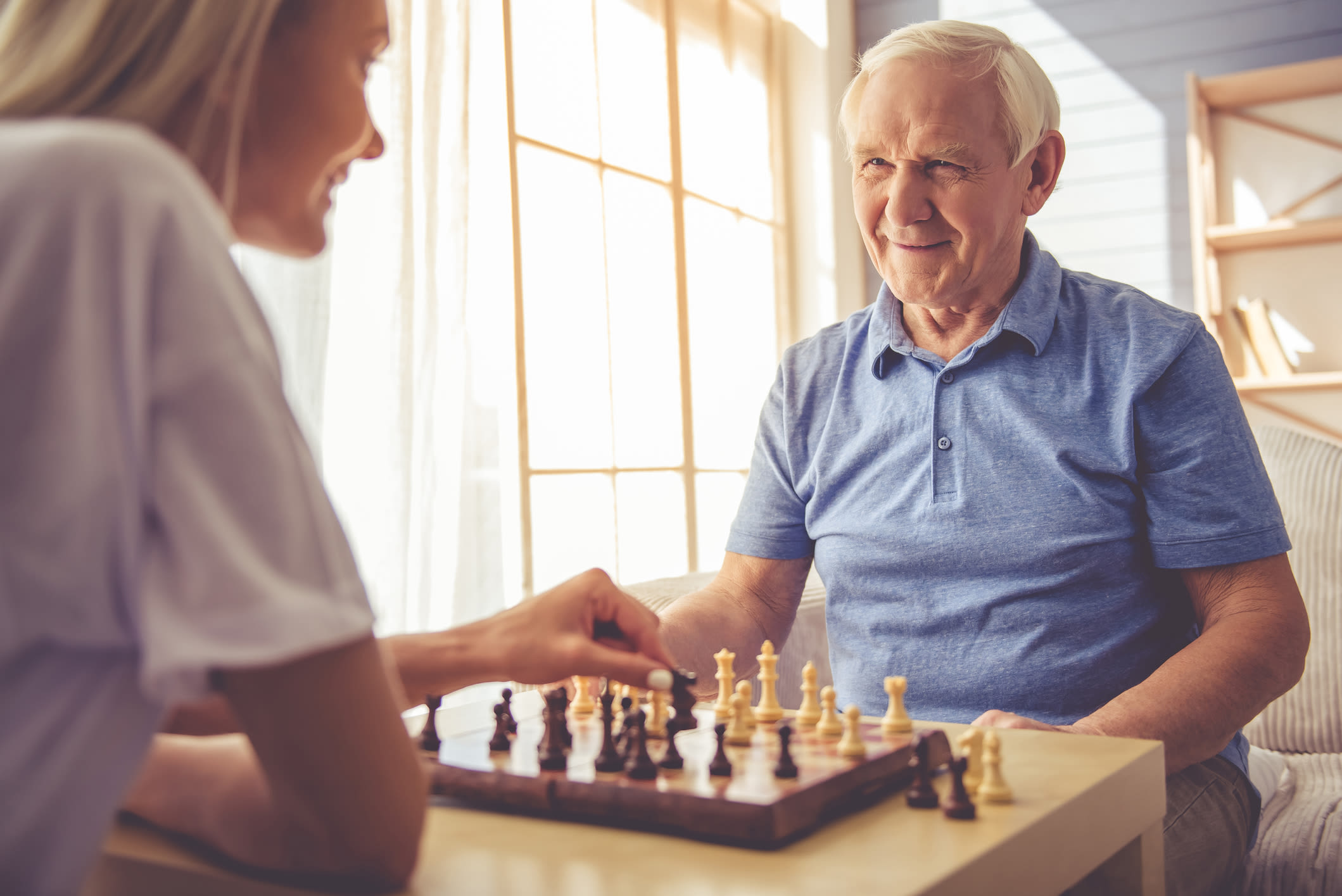 Resident and a younger woman playing chess at Serenity in East Peoria, Illinois