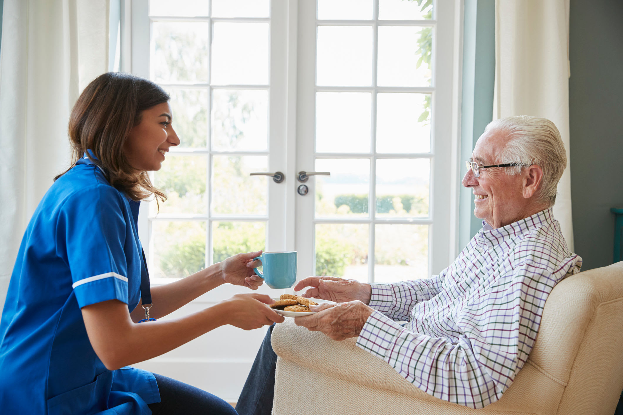 Caretaker delivering a drink to a resident at Serenity in East Peoria, Illinois