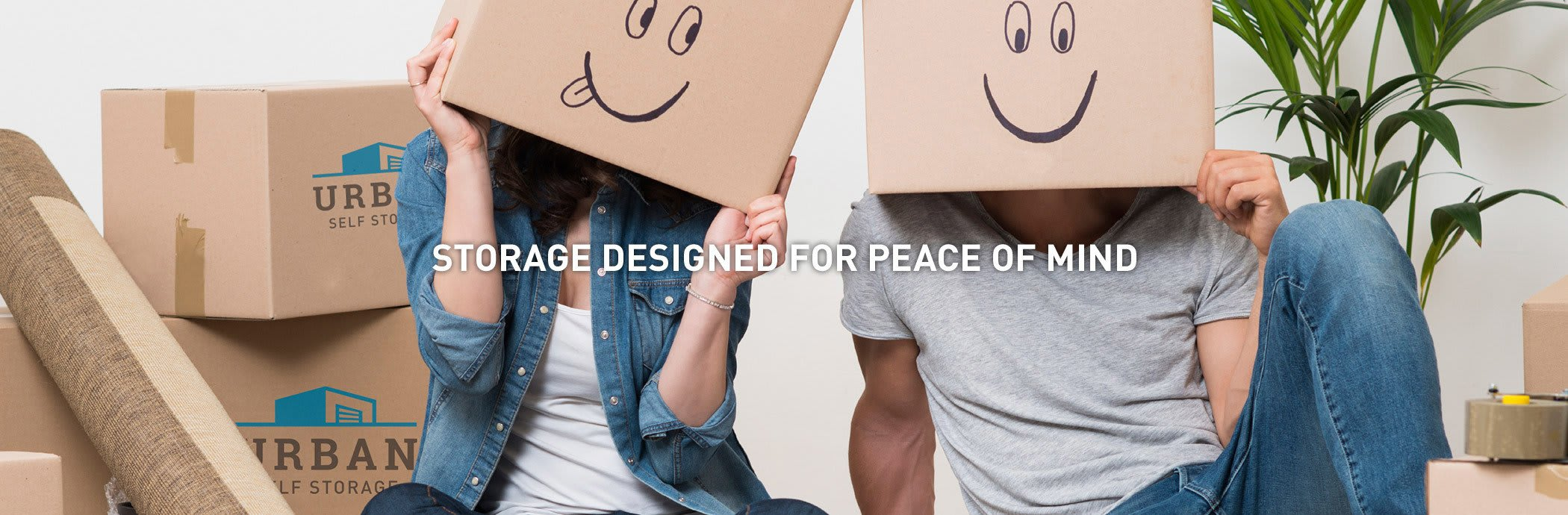A couple having fun with boxes after they were done packing their things to be stored at Fremont Heated Storage in Seattle, Washington