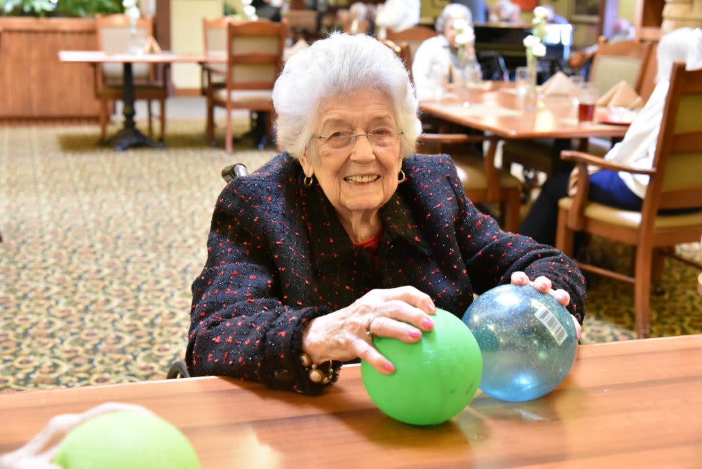 Resident sitting at a table holding colored balls at Quail Park Memory Care Residences of Visalia in Visalia, California