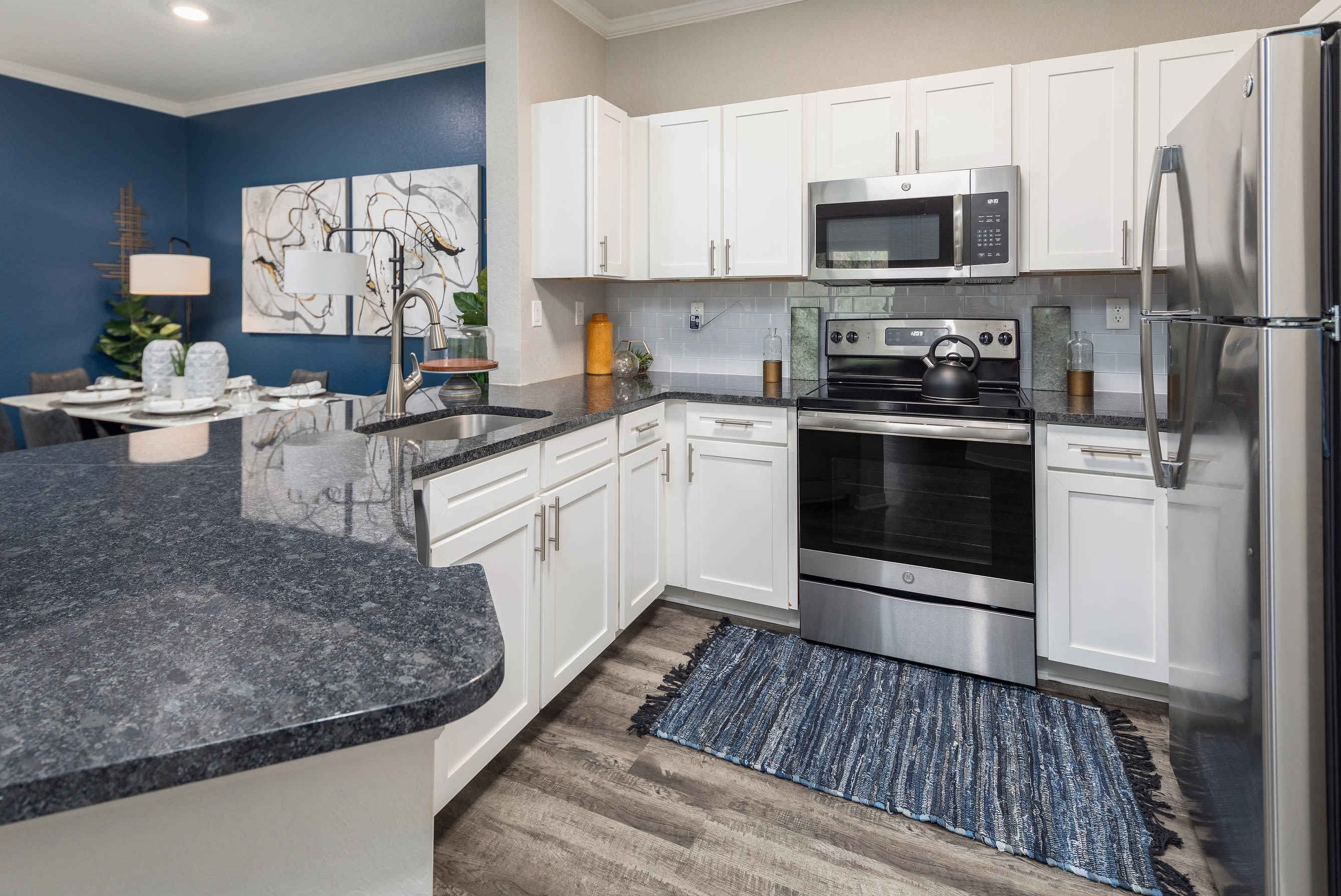 Open concept kitchen with granite countertops in a model home at Mezza in Jacksonville, Florida