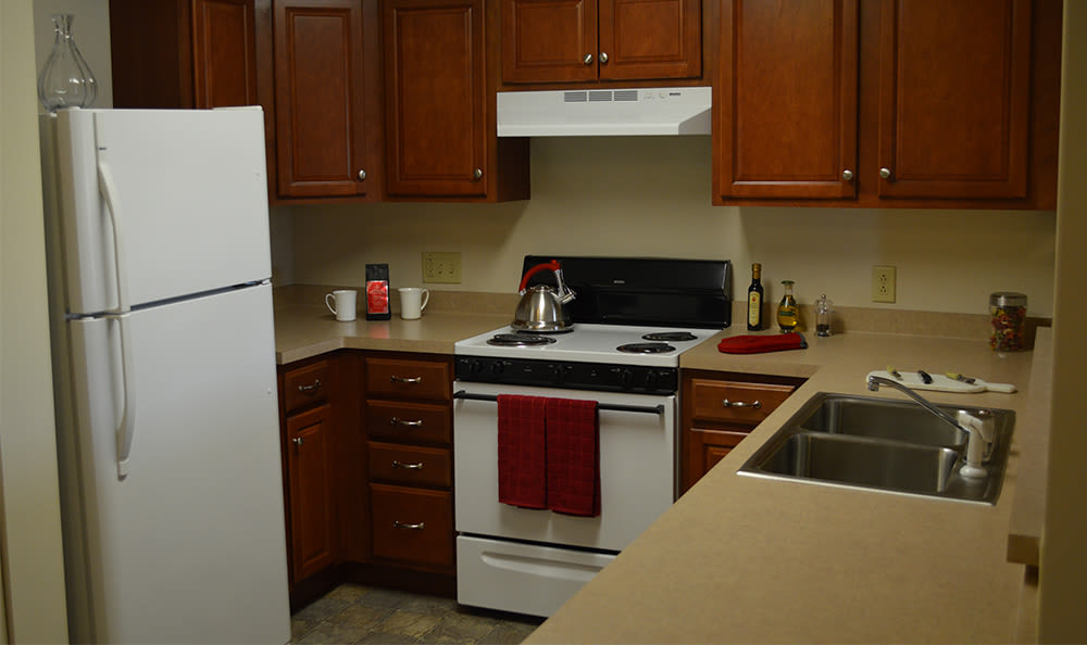 Fully-equipped kitchen at Greenwood Cove Apartments home in Rochester, New York