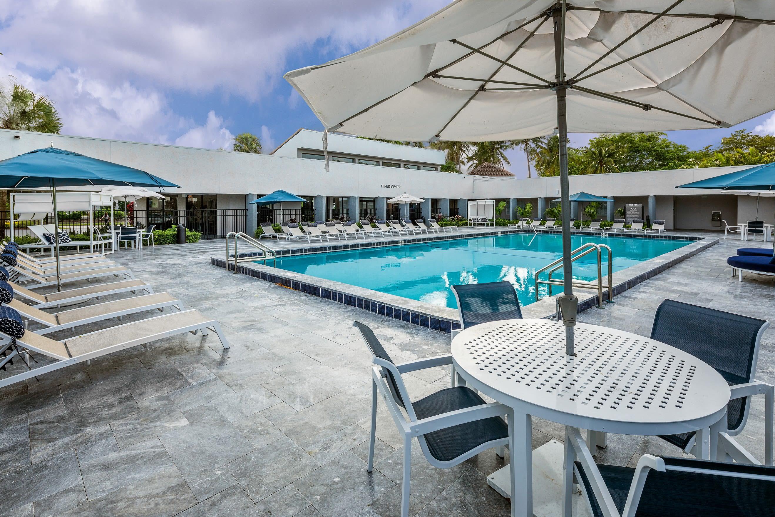 Poolside tables with umbrellas at Cielo Boca in Boca Raton, Florida