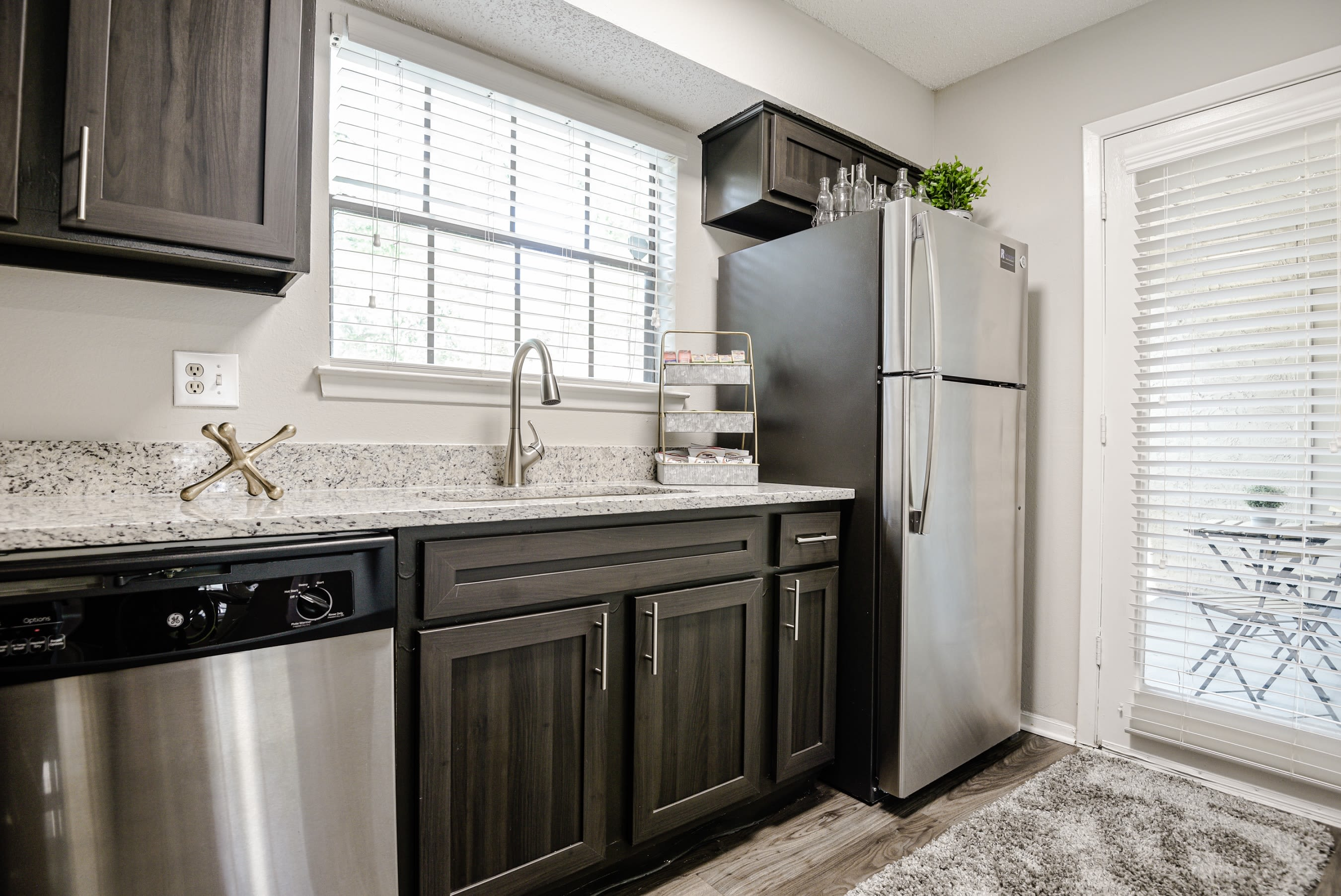 Modern kitchen with stainless steel appliances and granite countertops at The Regent in Dallas, Texas