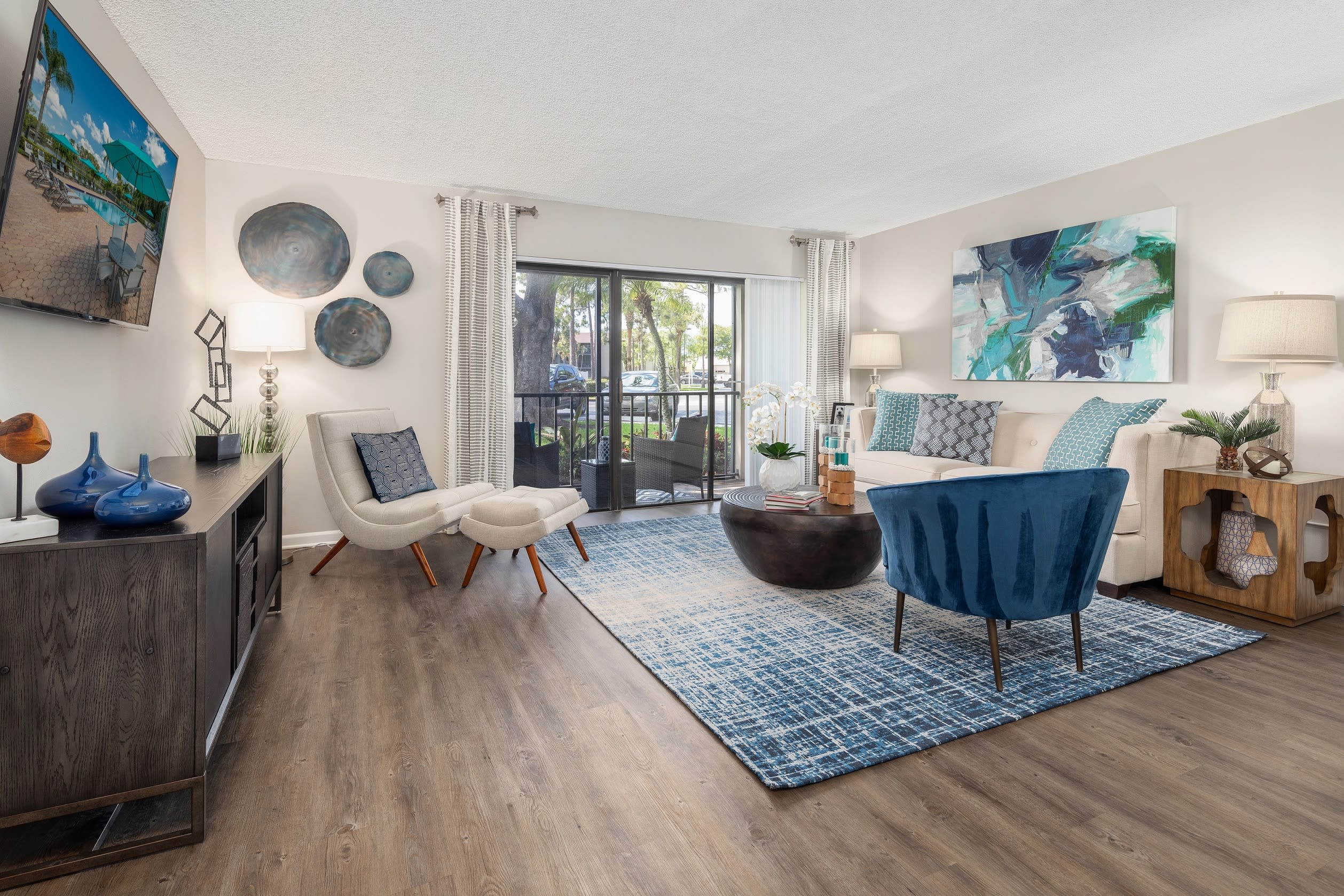 Open concept floor plan with hardwood floors and modern decor at Verse at Royal Palm Beach in Royal Palm Beach, Florida