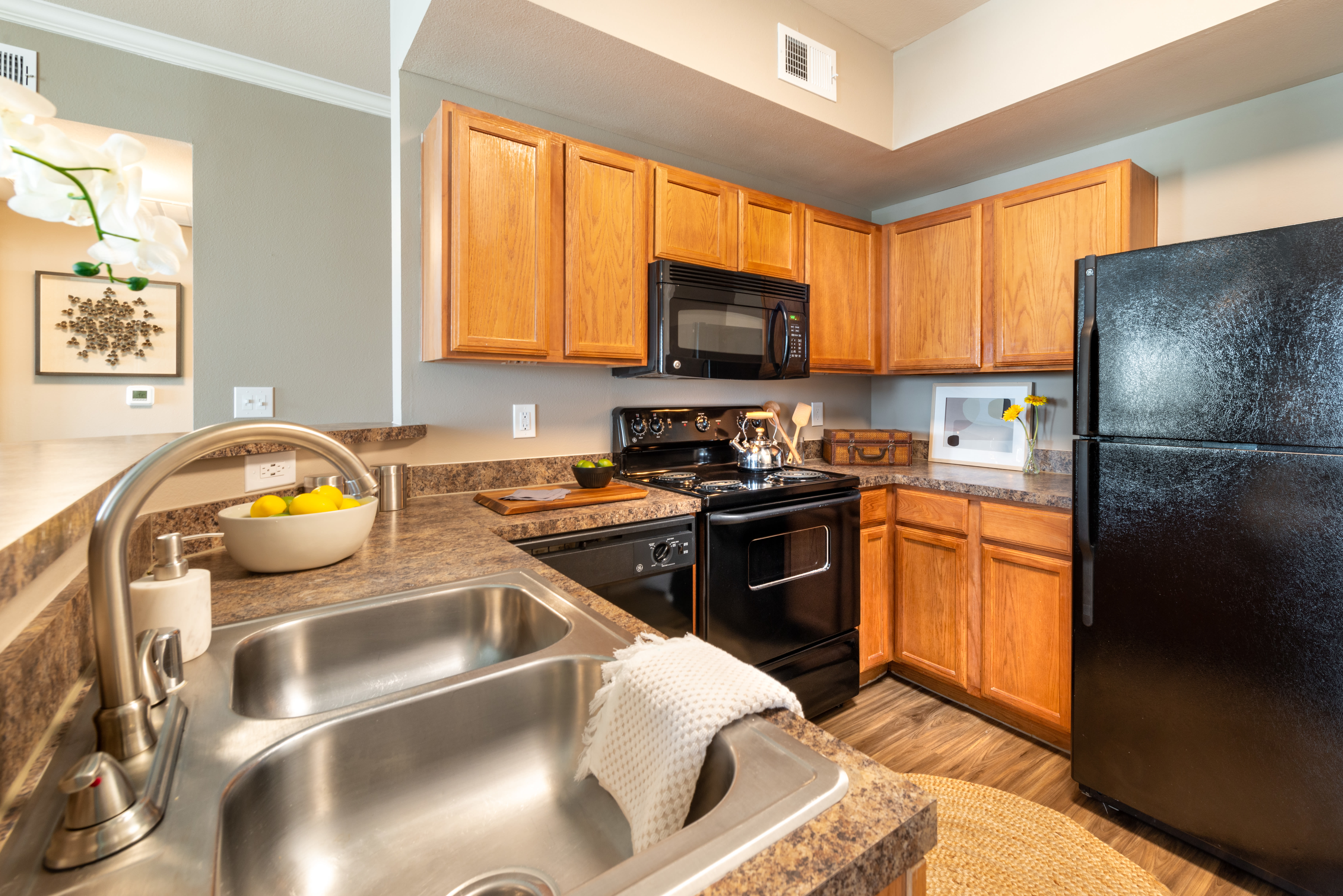 Hardwood flooring and cherry wood cabinetry in a model apartment's kitchen at Olympus Team Ranch in Benbrook, Texas