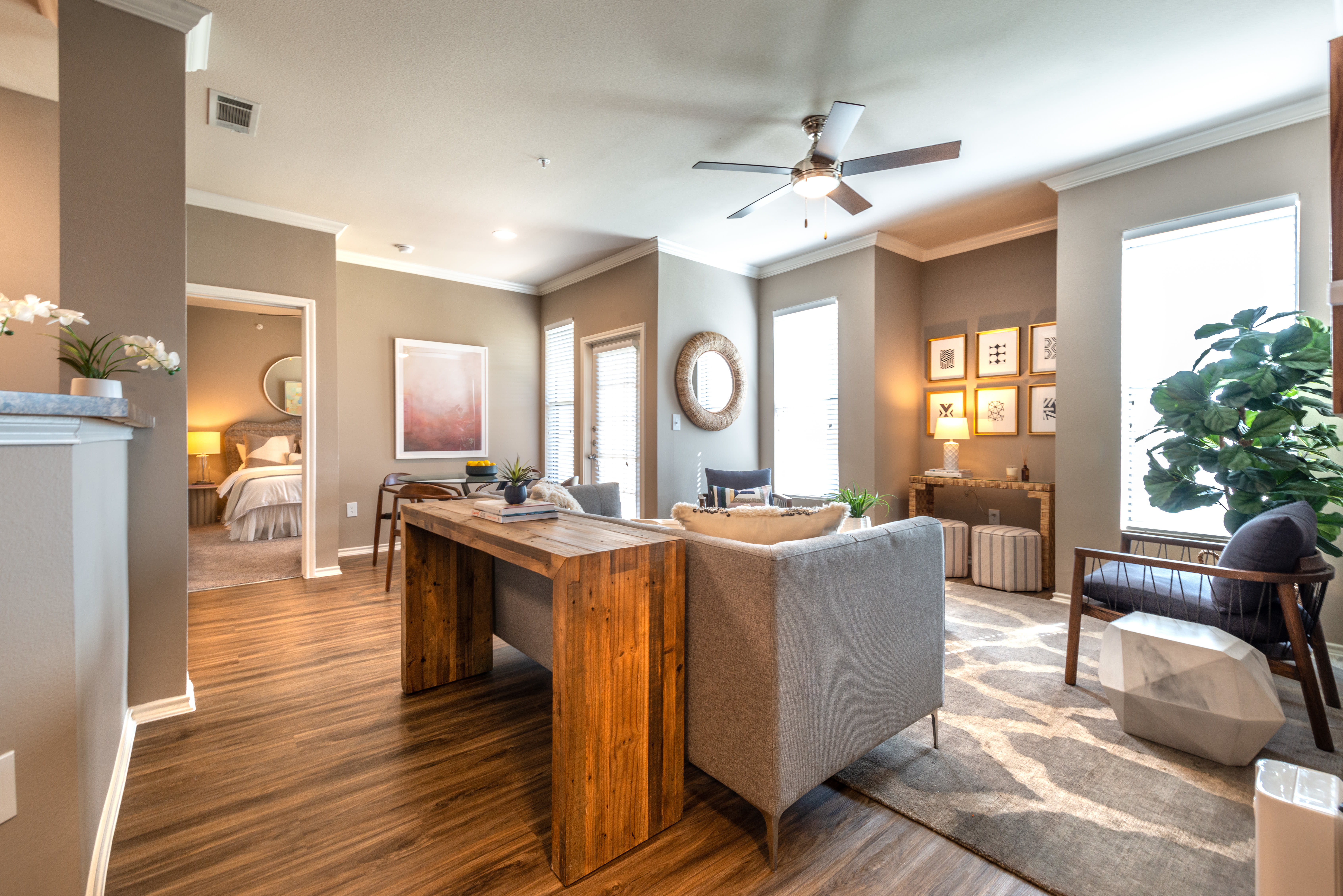 Open floor plan format with spacious living space and a ceiling fan in a model apartment's living area at Olympus Team Ranch in Benbrook, Texas