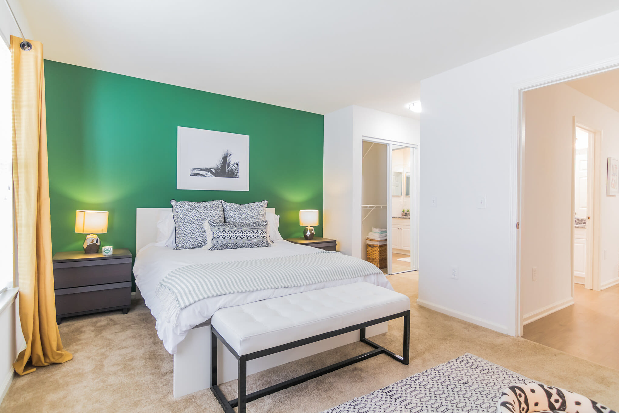 Green accent wall highlights this stylish bedroom with hardwood floors and ample natural light at Eagle Rock Apartments at Freehold in Freehold, New Jersey