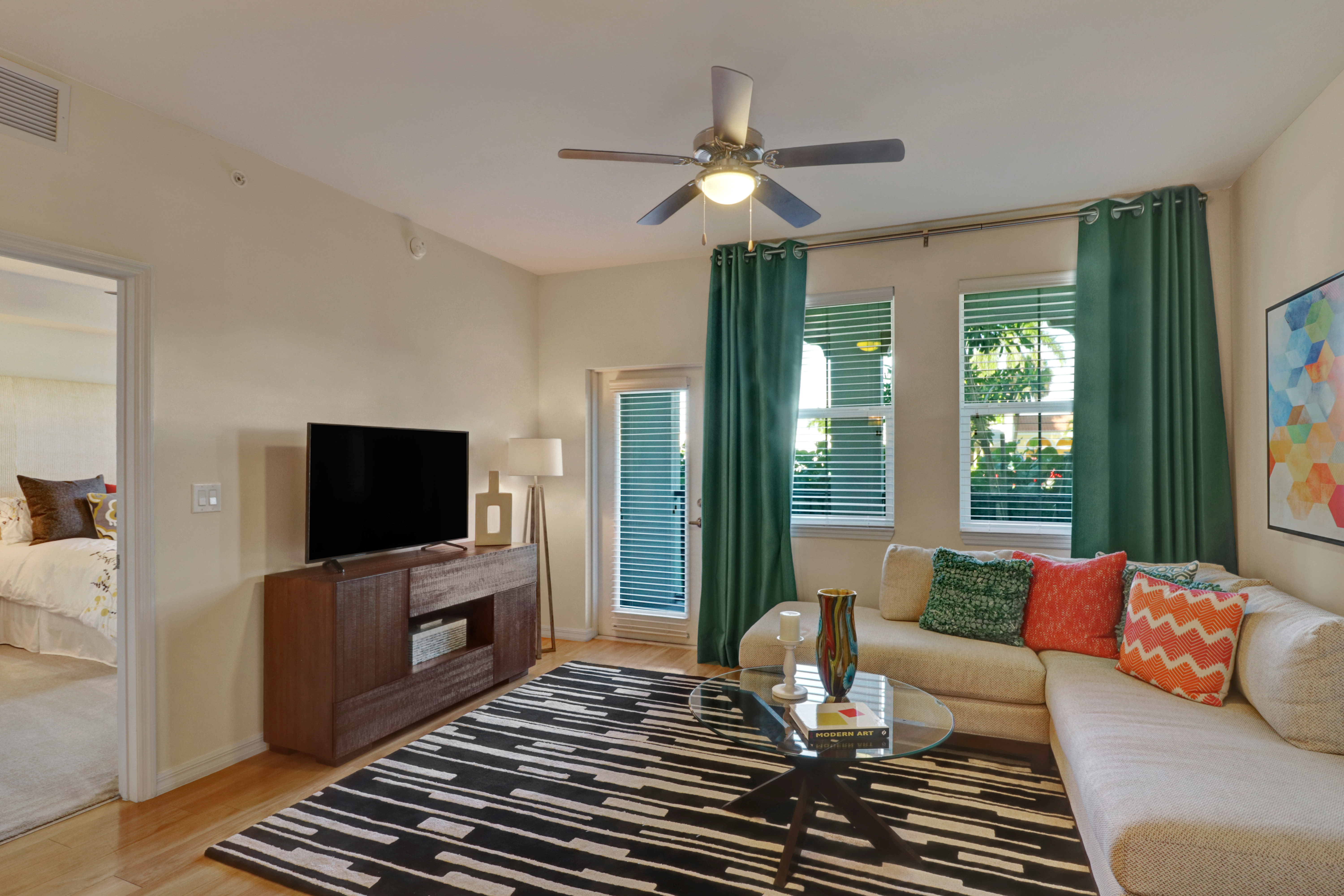 Living room featuring big windows in hardwood flooring at Linden Pointe in Pompano Beach, Florida