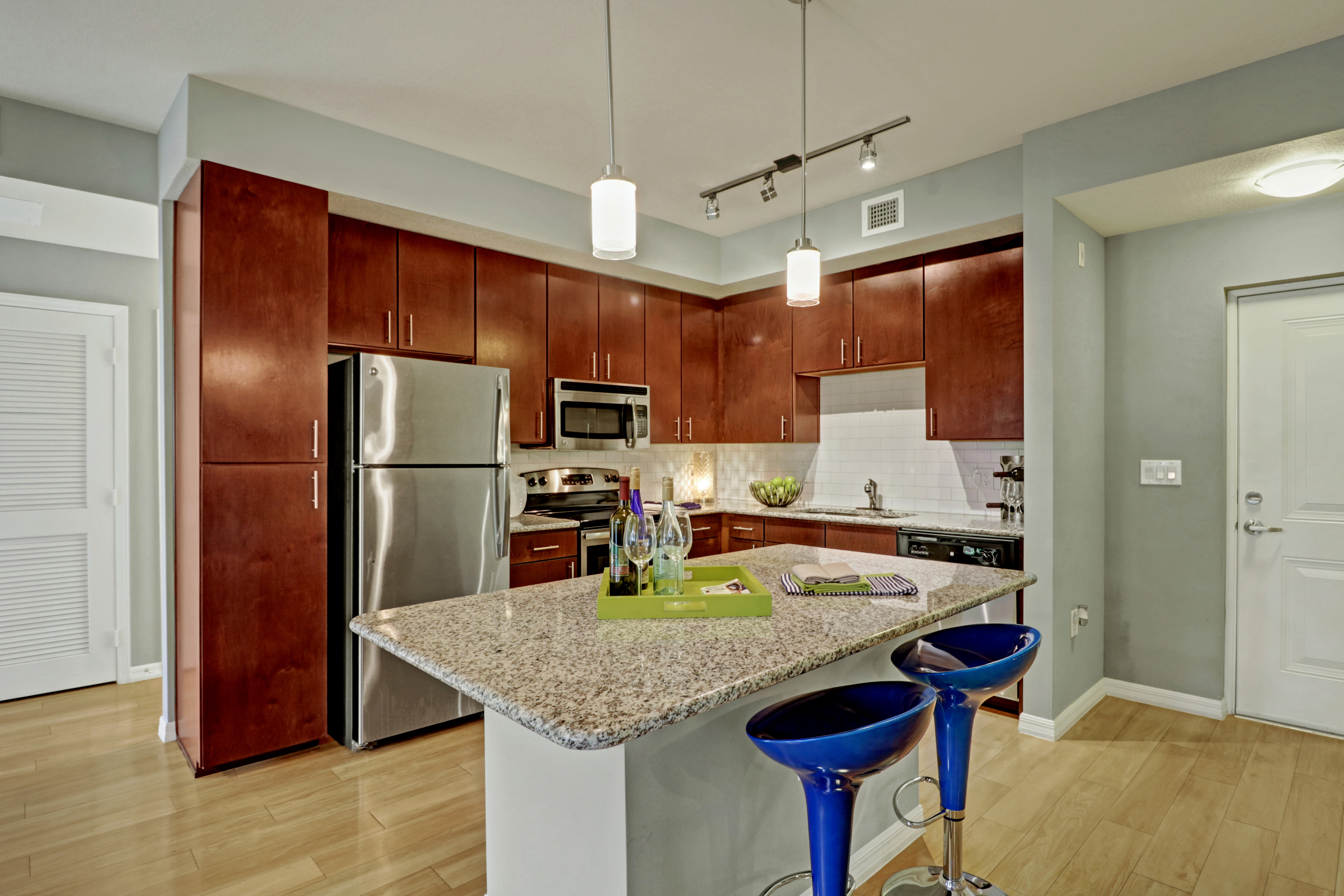Kitchen at Linden Pointe in Pompano Beach, Florida features an island with barstool seating