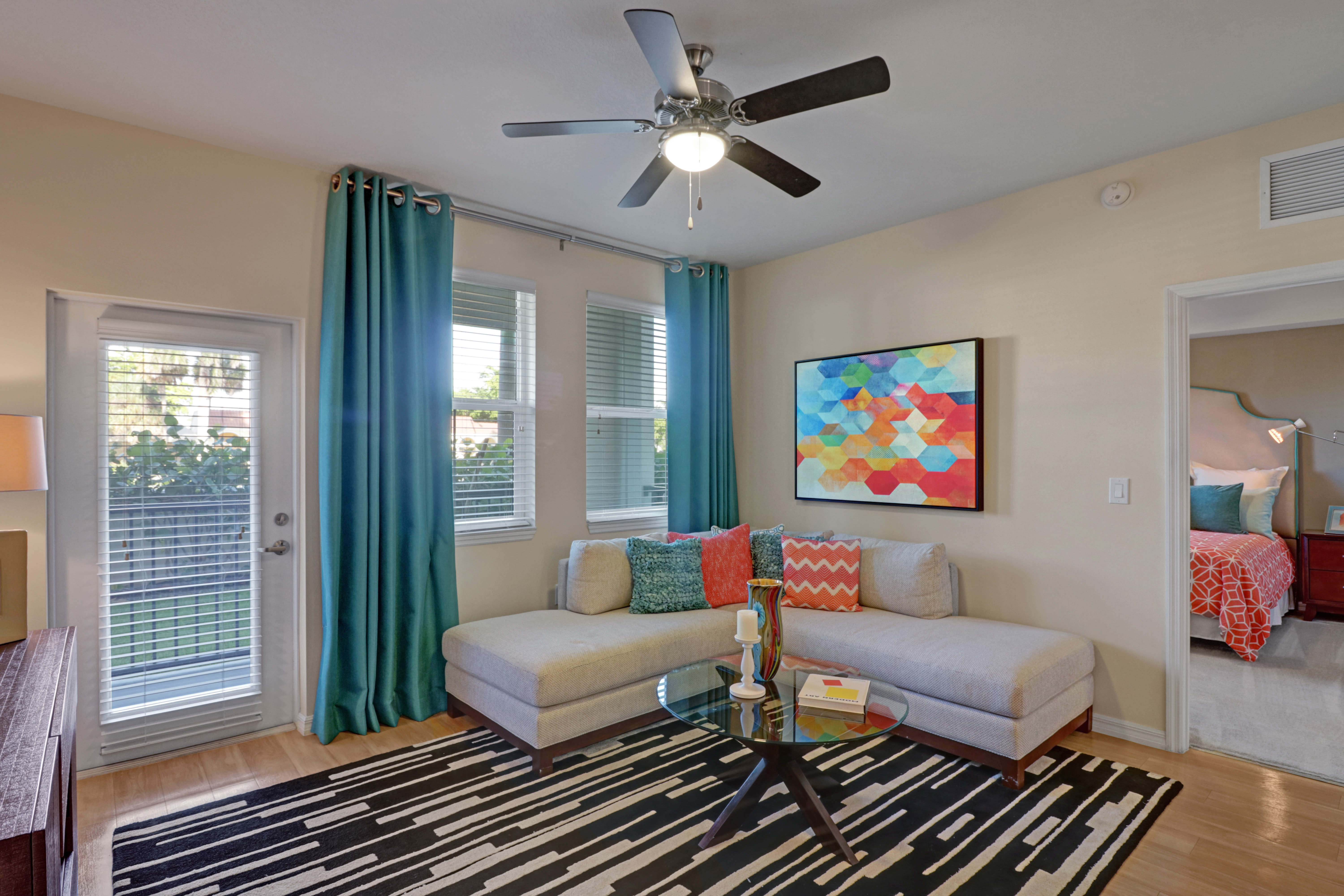 Corner couch in living room at Linden Pointe in Pompano Beach, Florida has large windows supplying lots of natural light