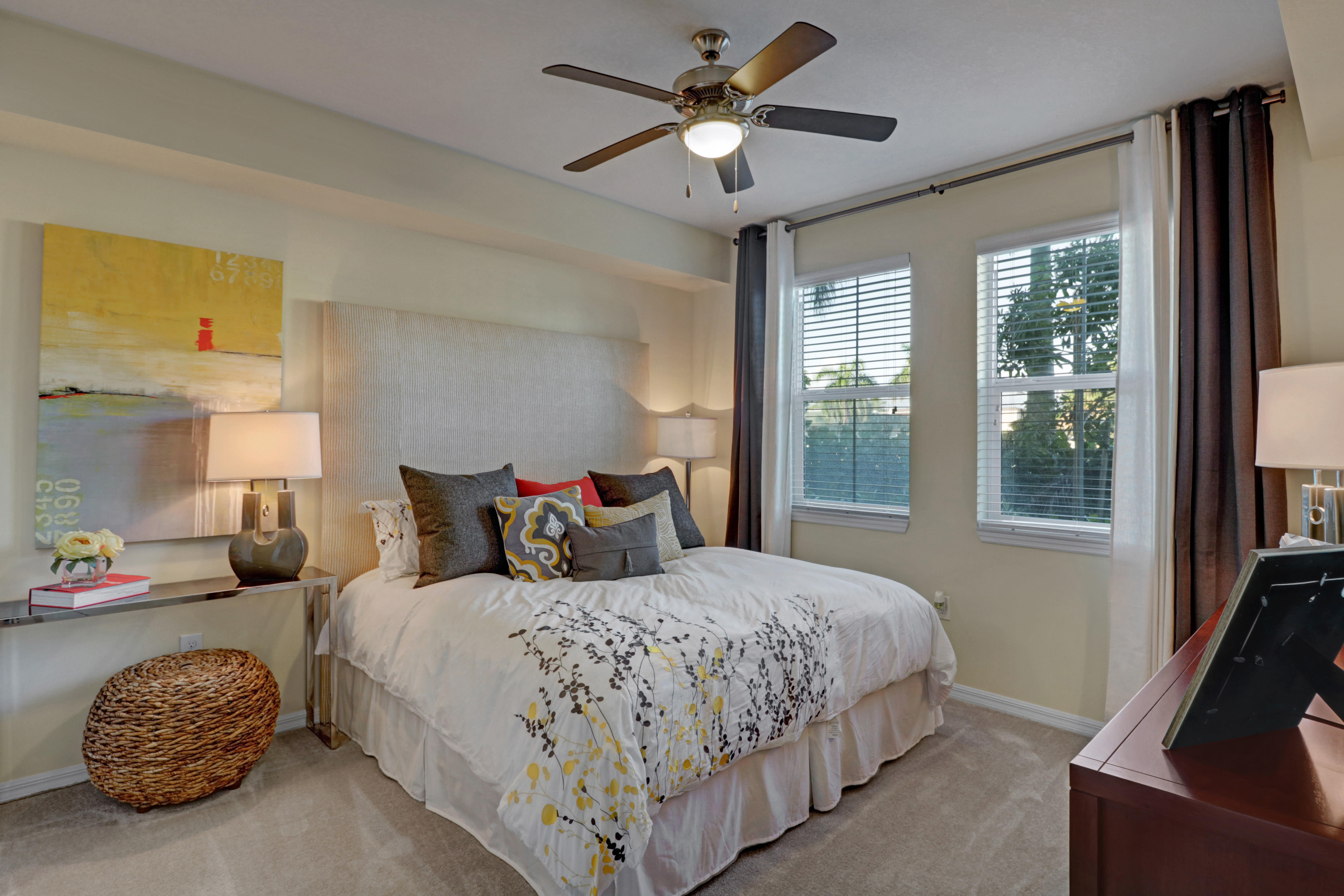 Bedroom at Linden Pointe features a ceiling fan and large windows