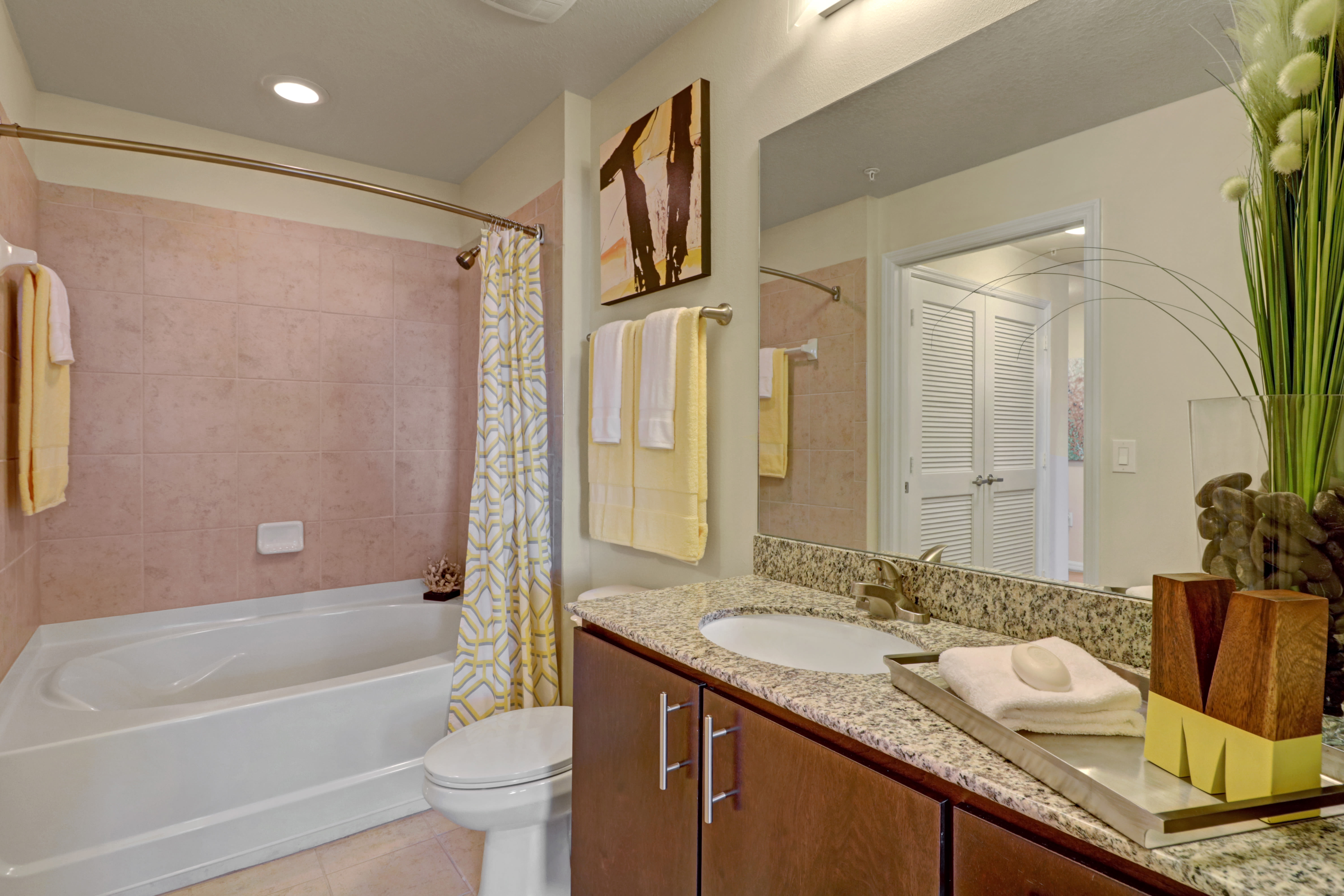 Bathroom featuring large vanity mirror and shower bathtub at Linden Pointe in Pompano Beach, Florida