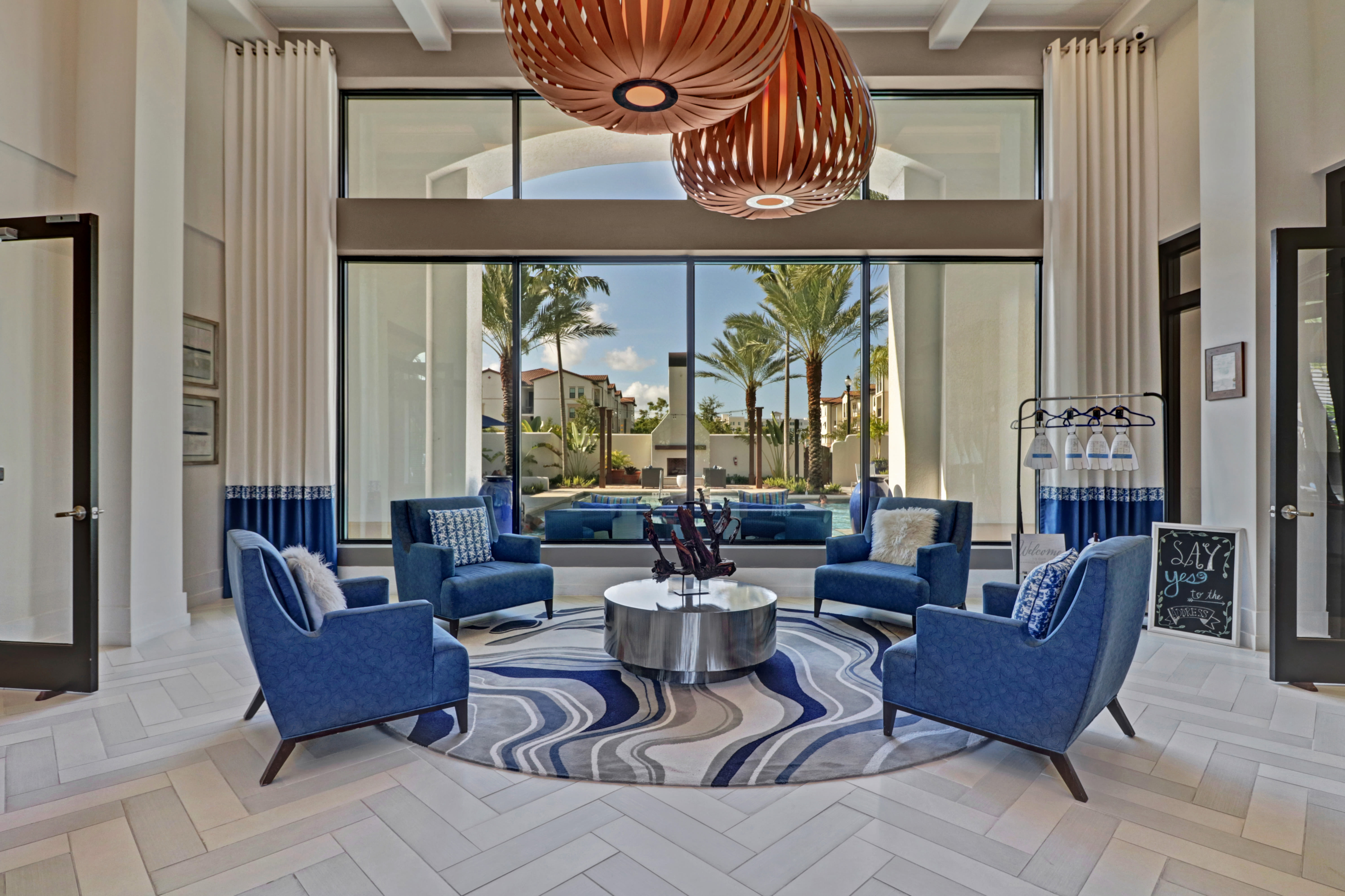Clubhouse sitting area  at Linden Pointe in Pompano Beach, Florida features blue chairs and unique coffee table