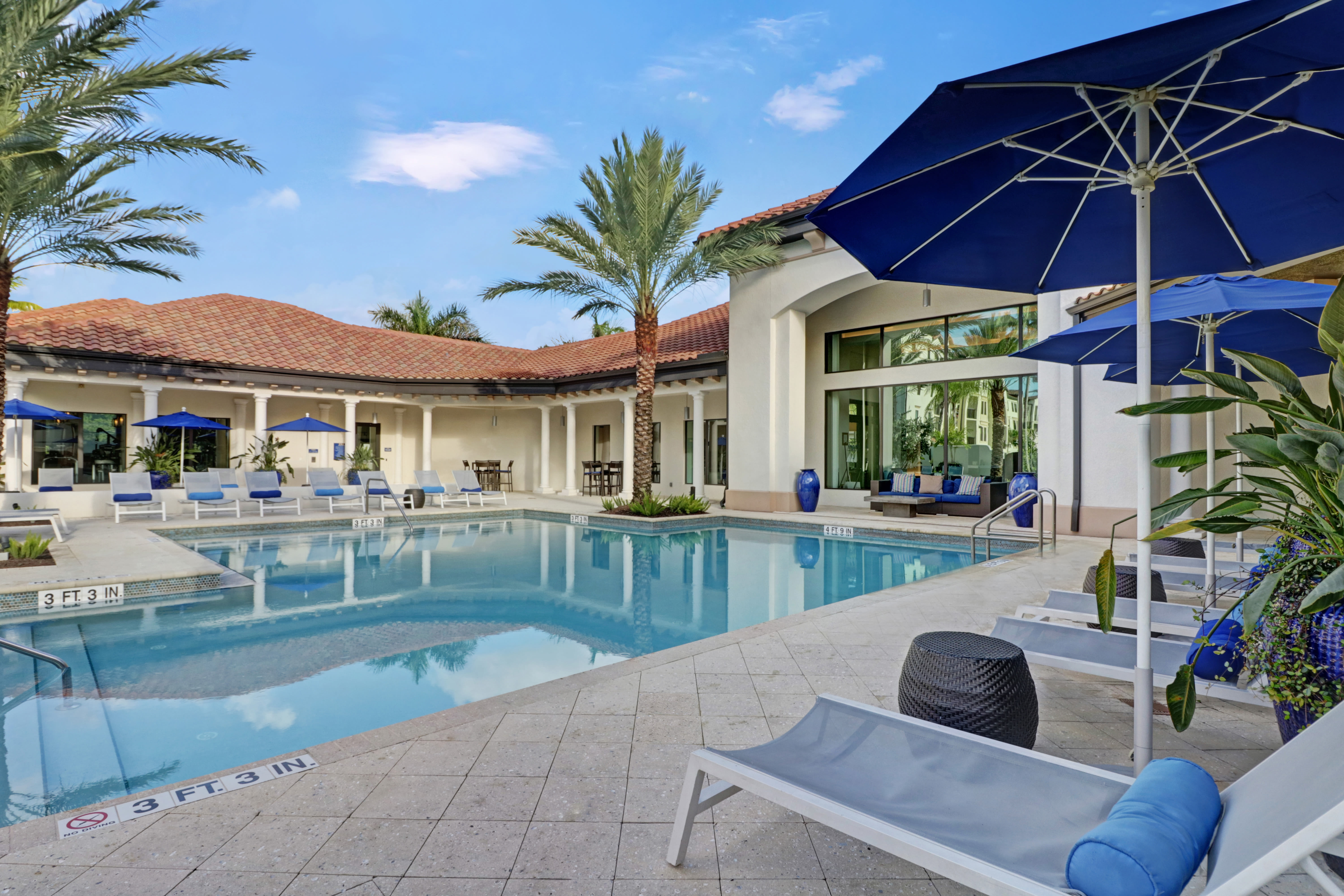 Lounge chair and shade umbrellas by community pool at Linden Pointe in Pompano Beach, Florida