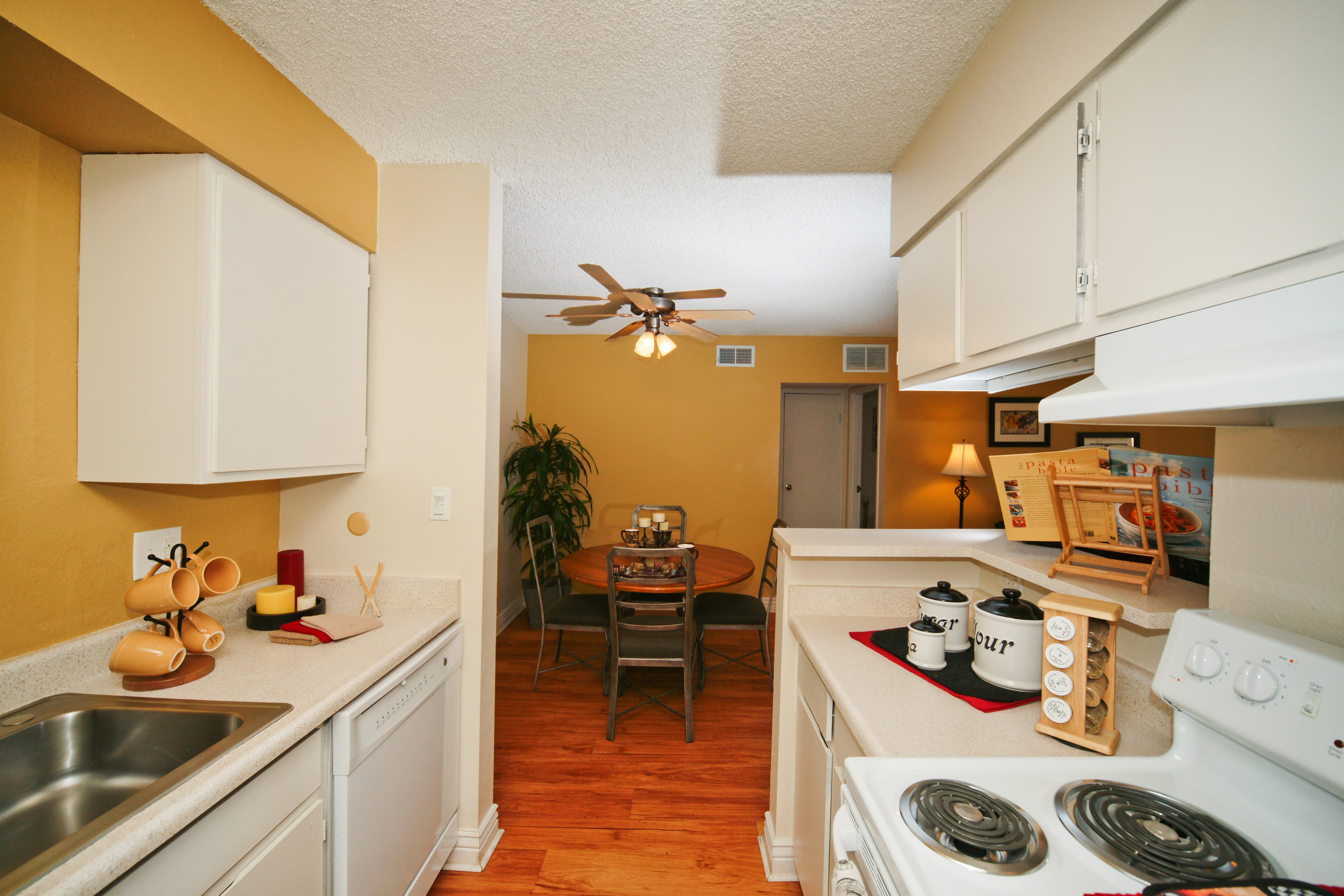 Dining space with ceiling fan outside of kitchen in an apartment at Hampden Heights Apartments in Denver, Colorado