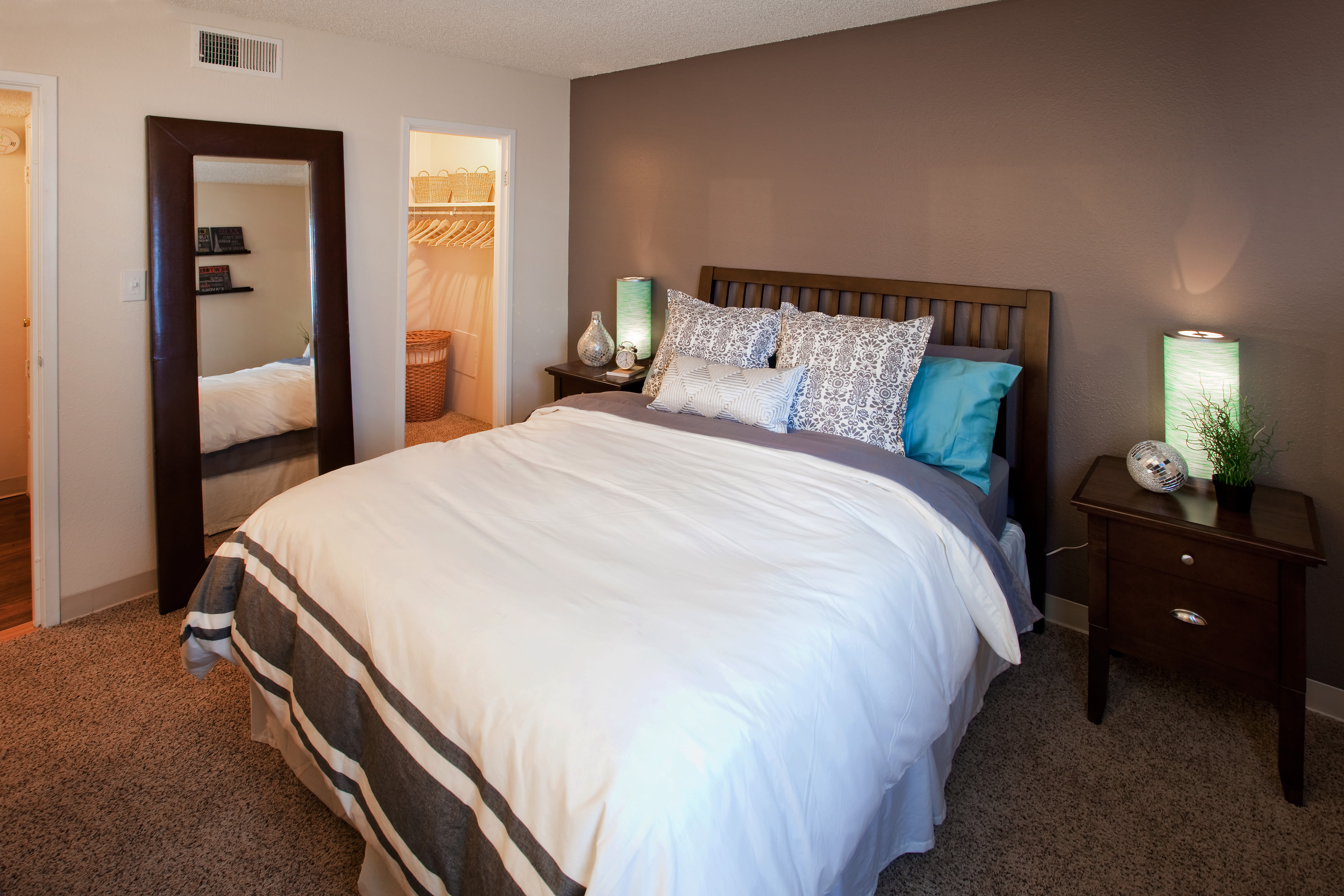 Bedroom at Hampden Heights Apartments features a gray accent wall and full length mirror