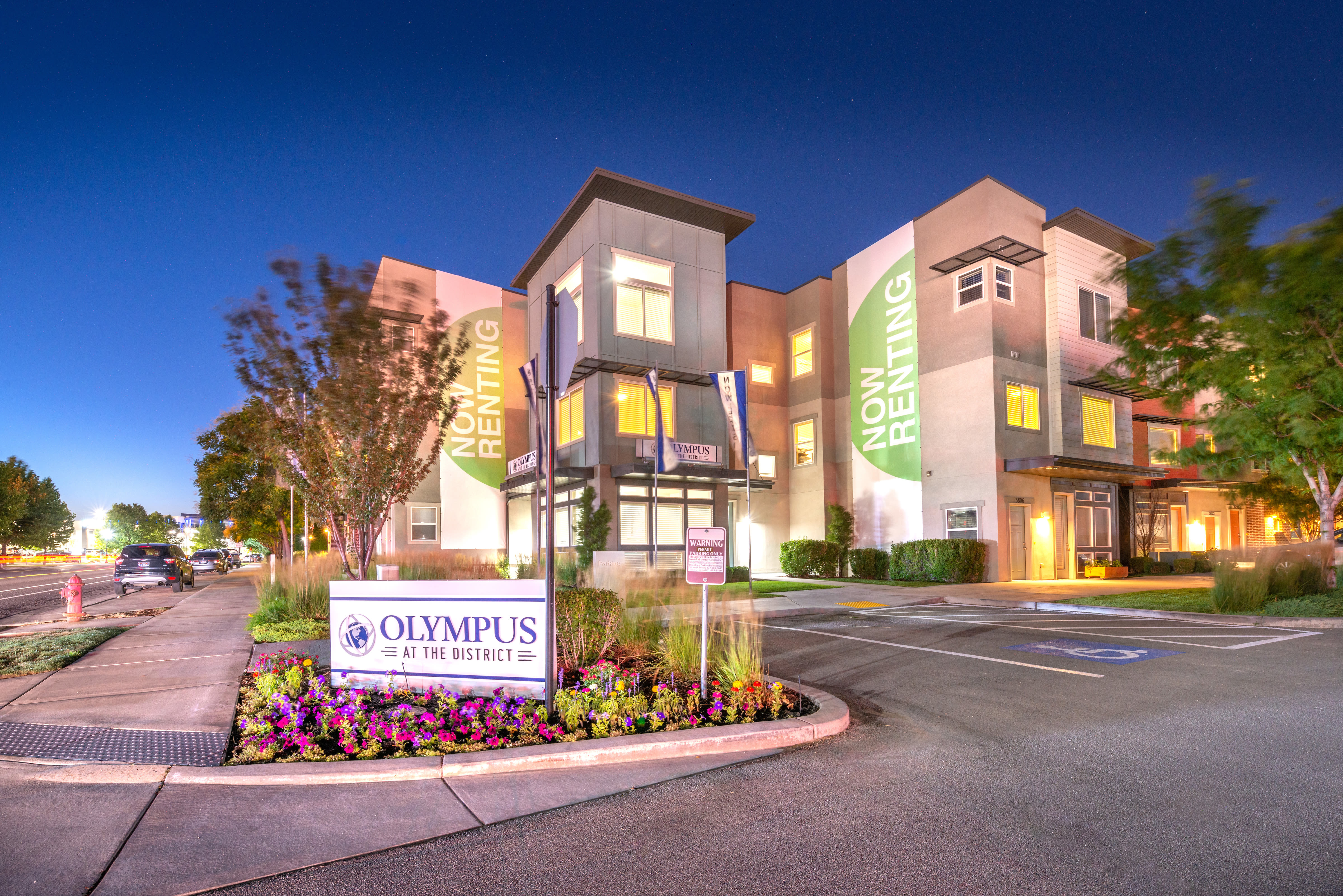 Exterior of buildings at Olympus at the District in South Jordan, Utah lit up in early evening.