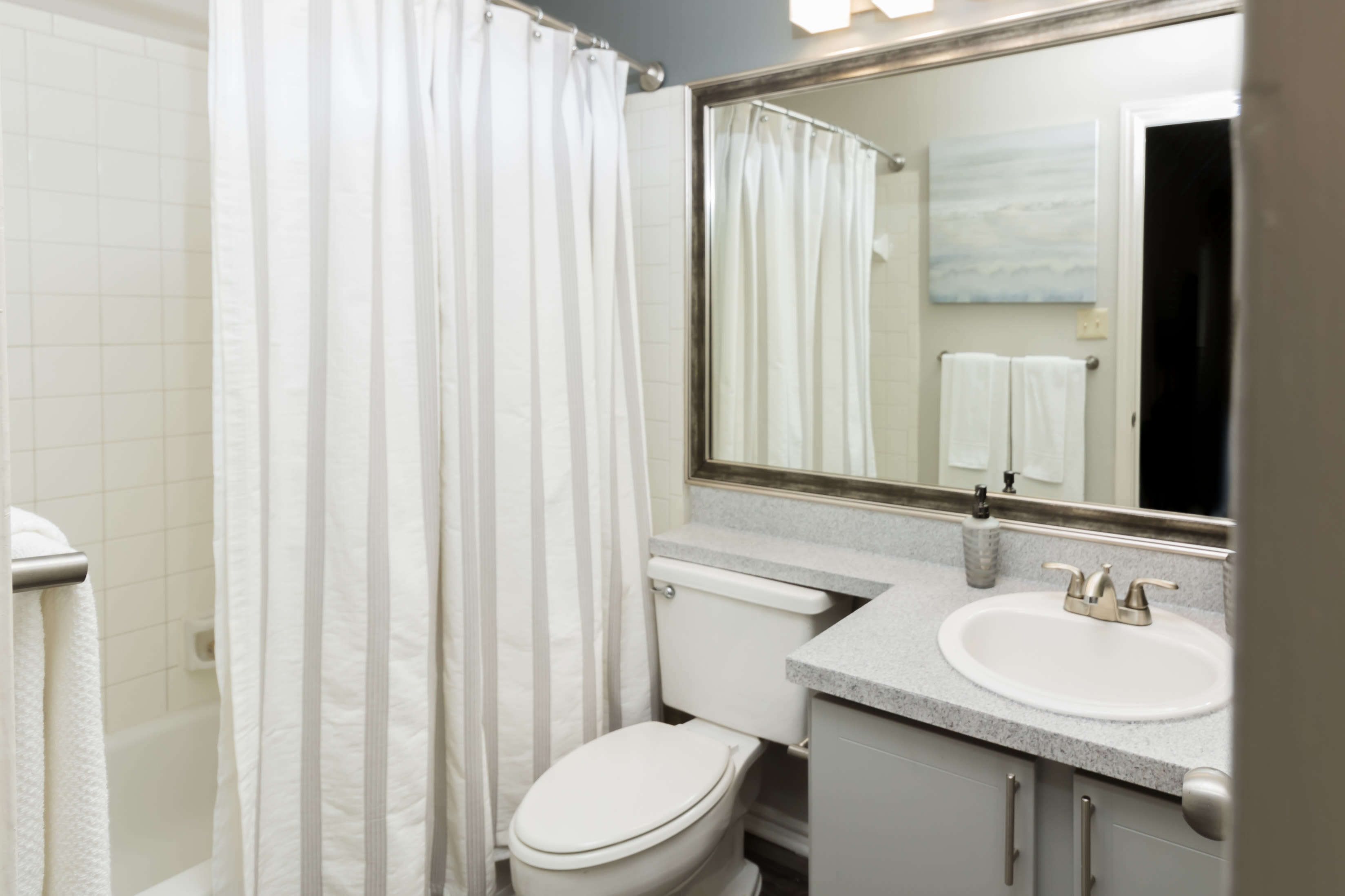 Bathroom with large mirror and cute vanity at The Logan in Bedford, Texas