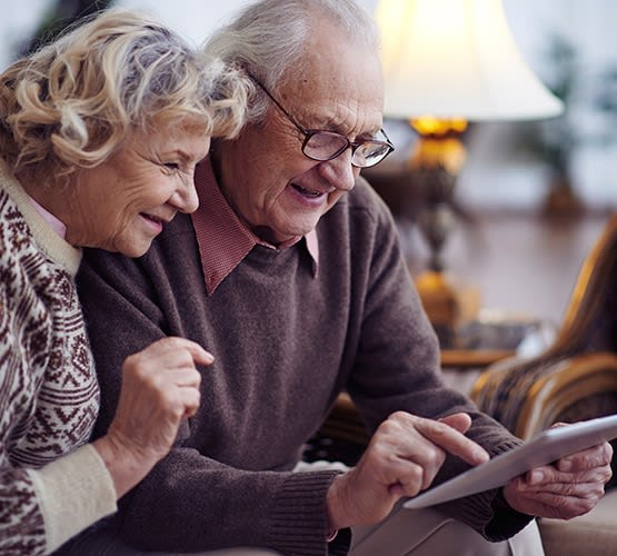 Senior couple ecstatic signing up for a tour at Grand Villa of Palm Coast in Palm Coast, Florida.