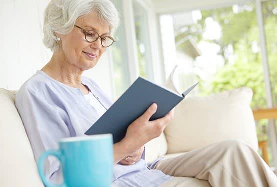 Senior woman enjoying a good book at Grand Villa of Palm Coast in Palm Coast, Florida