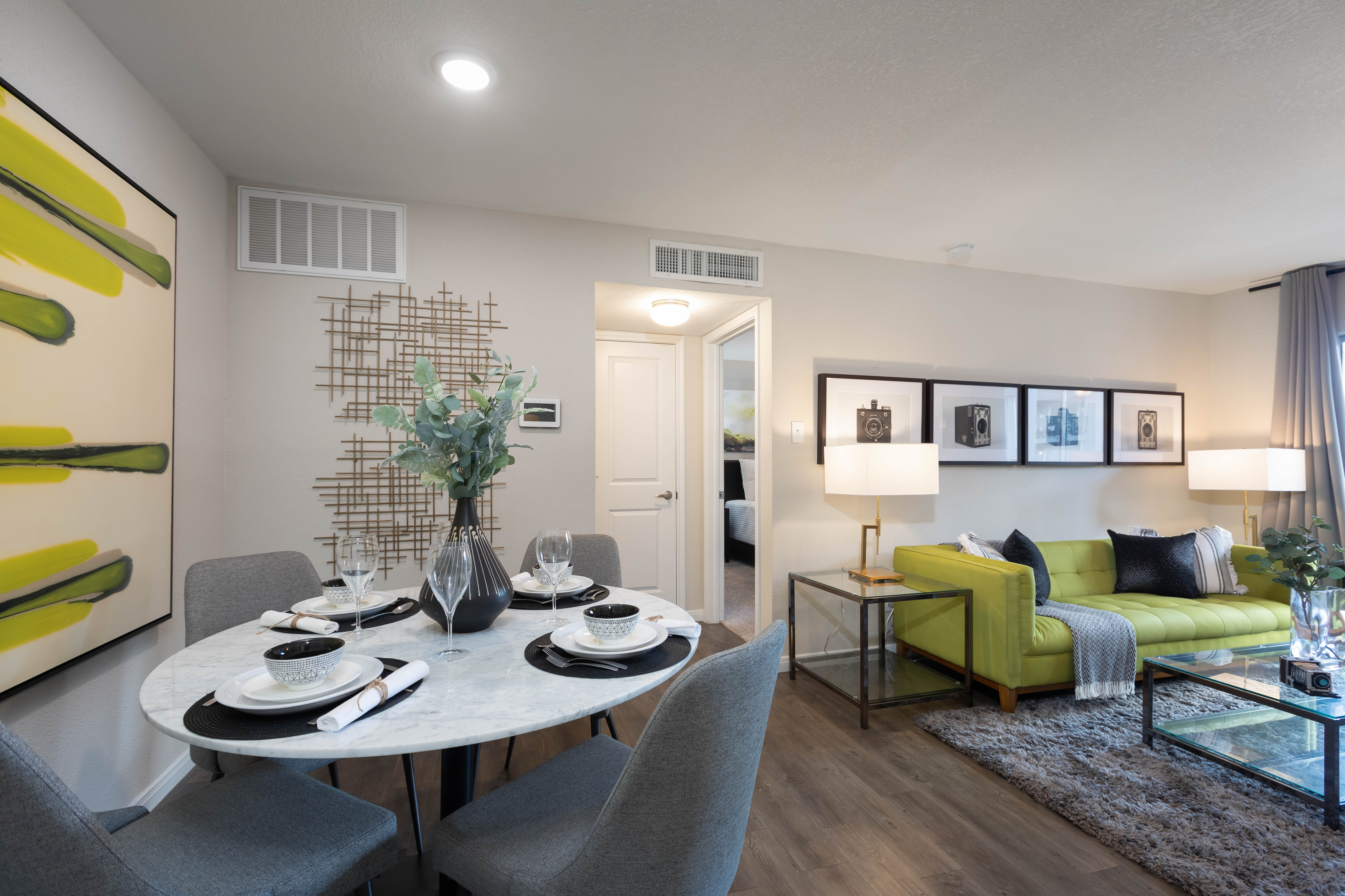 Open-concept floor plan with hardwood floors and accent wall in the living area of model home at Lodge @ 1550 in Katy, Texas