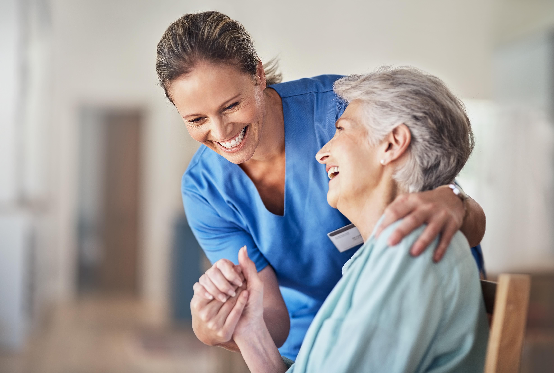 A woman helps a man in a wheelchair at Broadwell Senior Living in Kearney, Nebraska