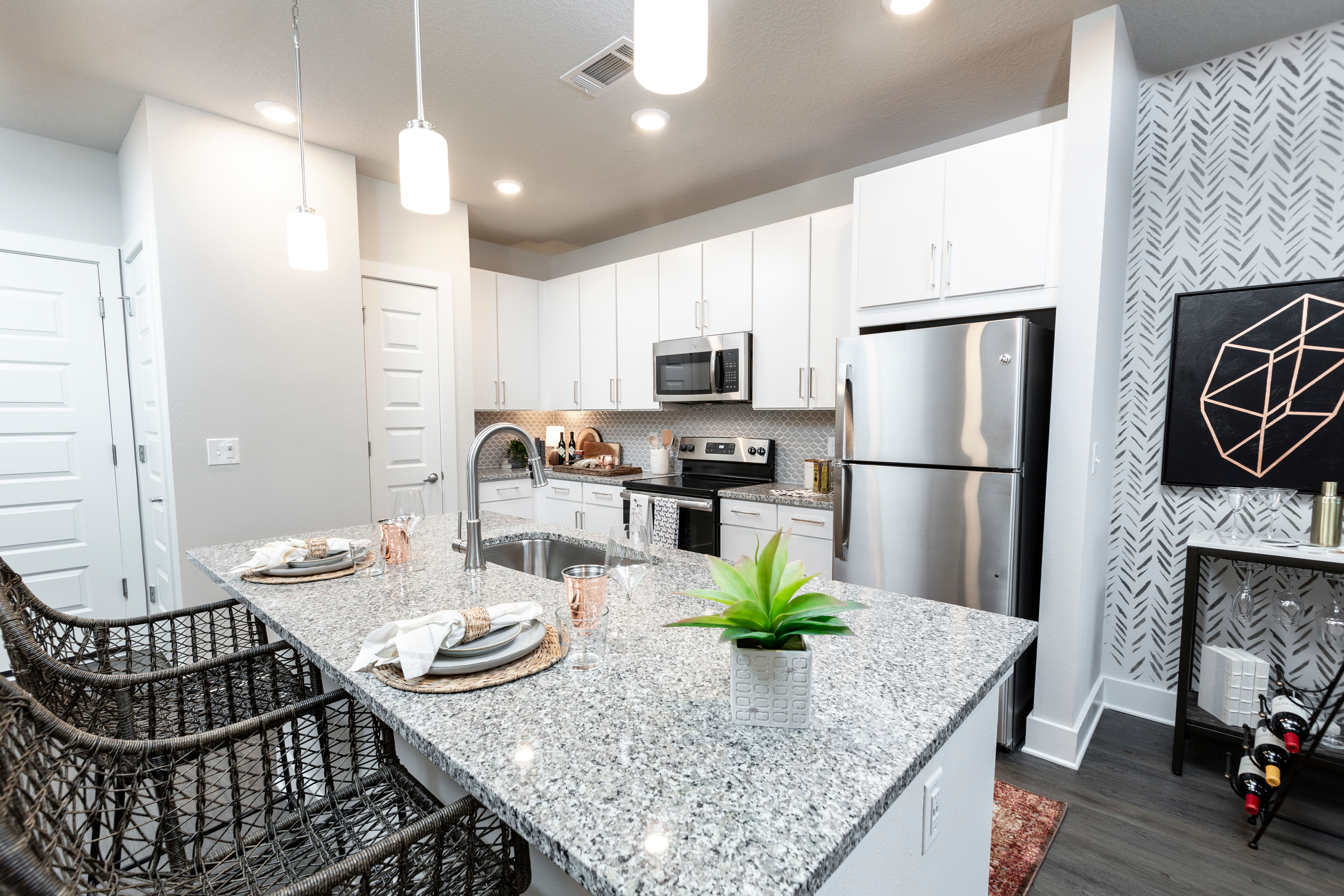 Beautiful open-concept home with a chef-inspired kitchen and hardwood floors at Parc at Wesley Chapel in Wesley Chapel, Florida