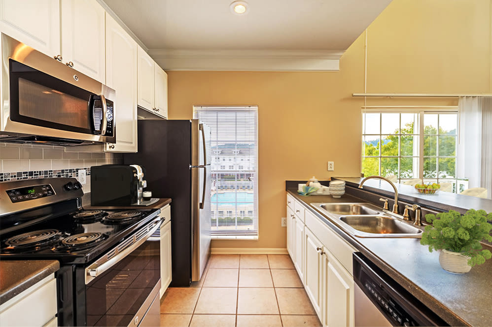 Tiled kitchen with white cabinets at The Waterfront Apartments & Townhomes in Munhall, Pennsylvania
