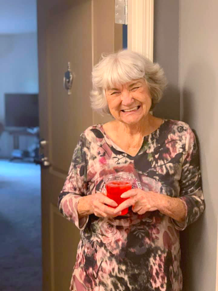 Resident standing in her doorway holding a drink at Oxford Villa Active Senior Apartments in Wichita, Kansas