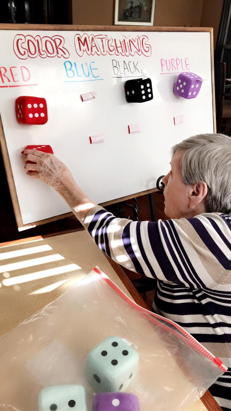 Resident playing a color matching game at Oxford Glen Memory Care at Sachse in Sachse, Texas