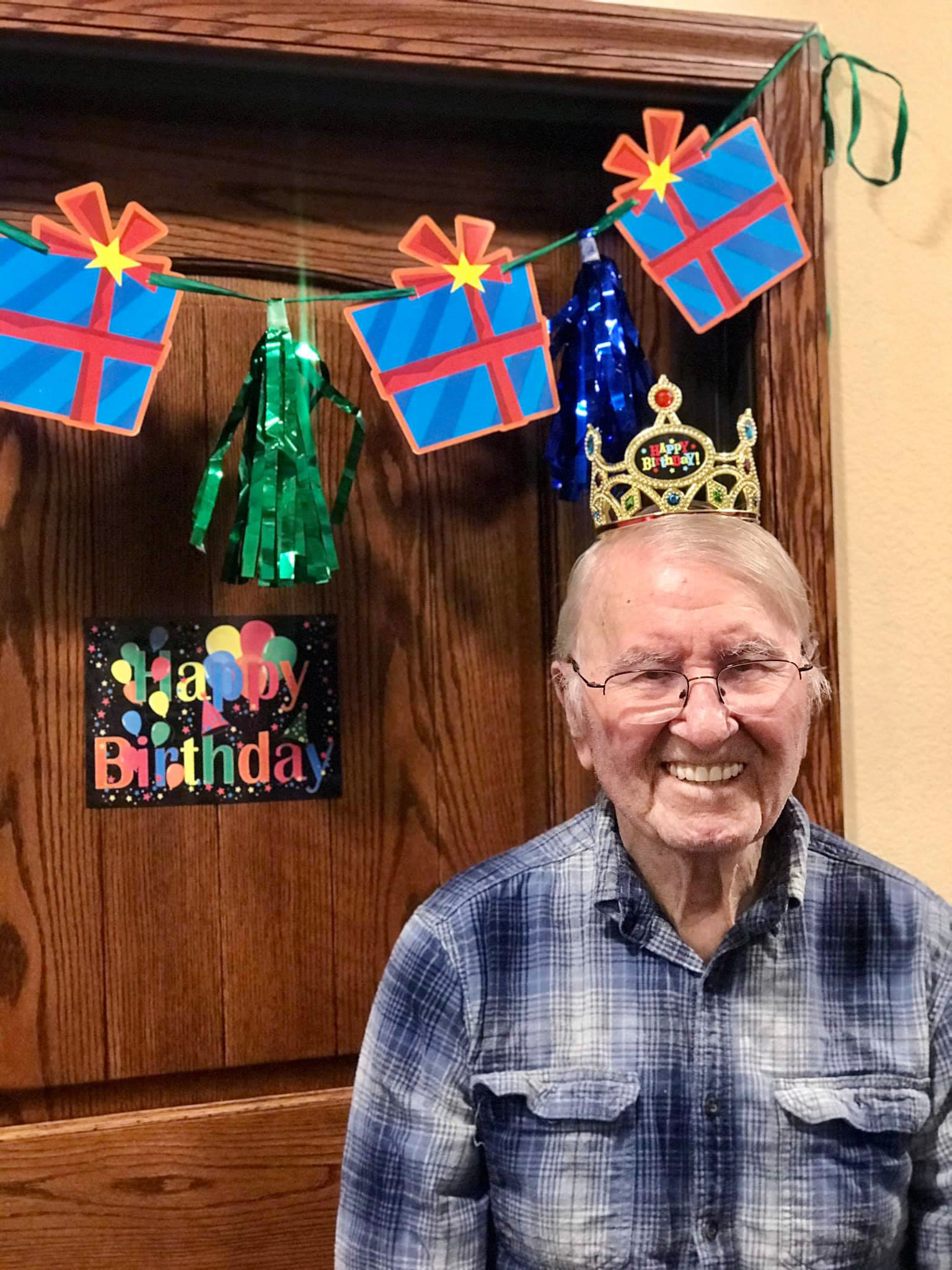 A resident smiling outside his apartment door, adorned with birthday decortations, at Oxford Glen Memory Care at Carrollton in Carrollton, Texas
