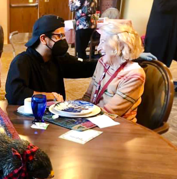 A masked member of the kitchen staff talking to a resident in the dining hall at The Oxford Grand Assisted Living & Memory Care in McKinney, Texas