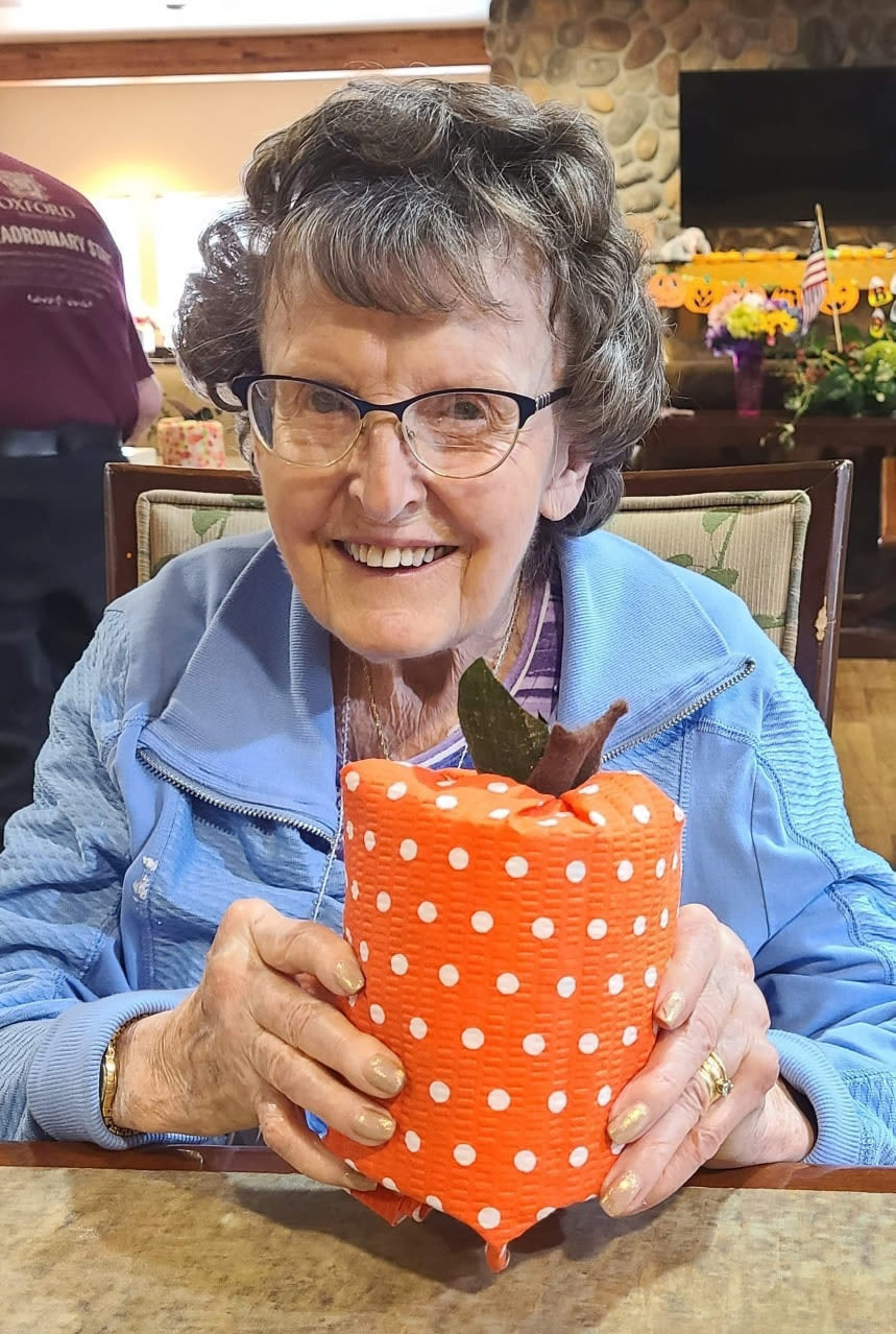 A resident receiving a wrapped gift at The Oxford Grand Assisted Living & Memory Care in Wichita, Kansas