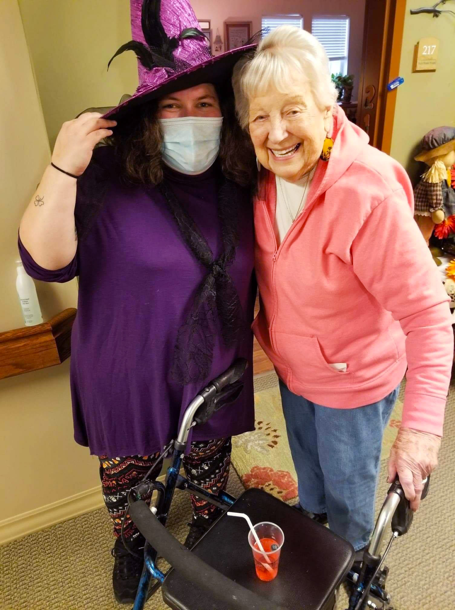 Masked caregiver in a witch costume side-hugging a resident at The Oxford Grand Assisted Living & Memory Care in Wichita, Kansas