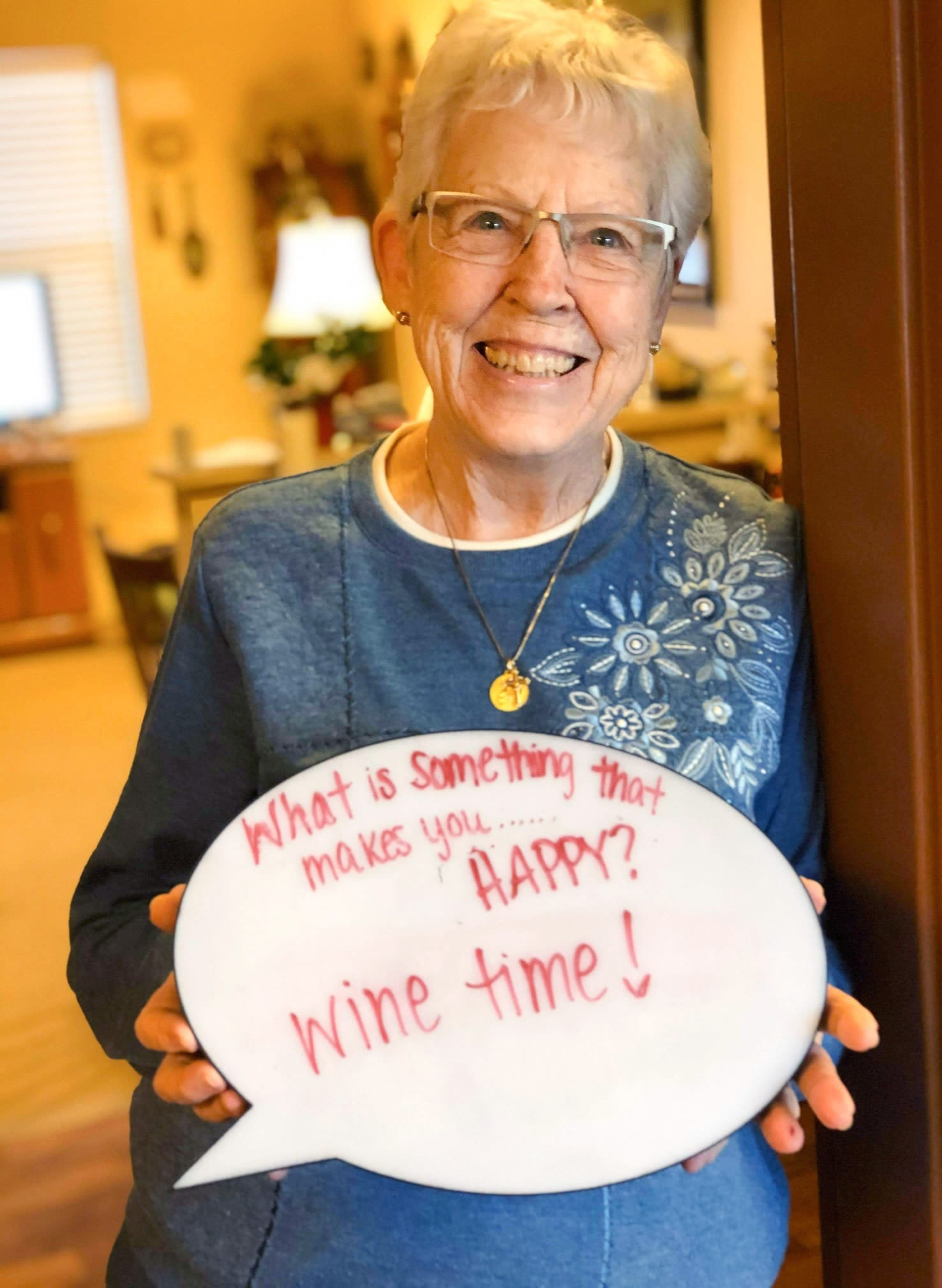 Resident holding a sign that says 'What makes you happy?: 'wine time!' at The Oxford Grand Assisted Living & Memory Care in Wichita, Kansas